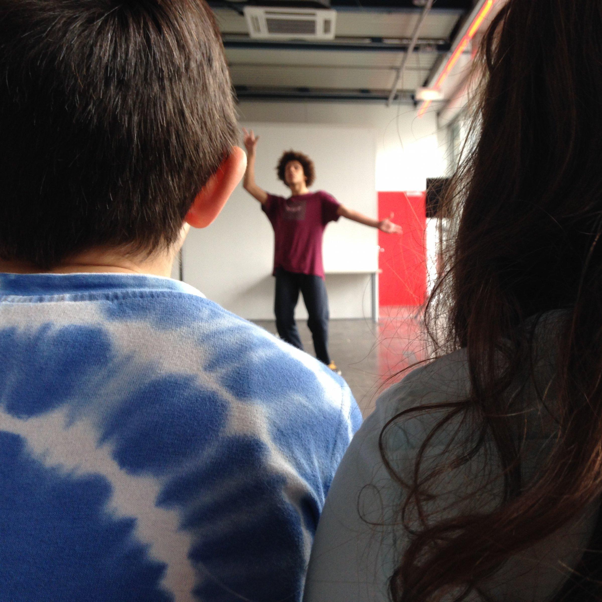 Das Bild zeigt im Vordergrund zwei Kinder, einen Jungen und ein Mädchen, zwischen denen hindurchfotografiert undeutlich zu sehen ist, was sie als Zuschauer*in bestaunen: einen Jugendlichen, der sich gerade auf einer improvisierten Bühne bewegt.