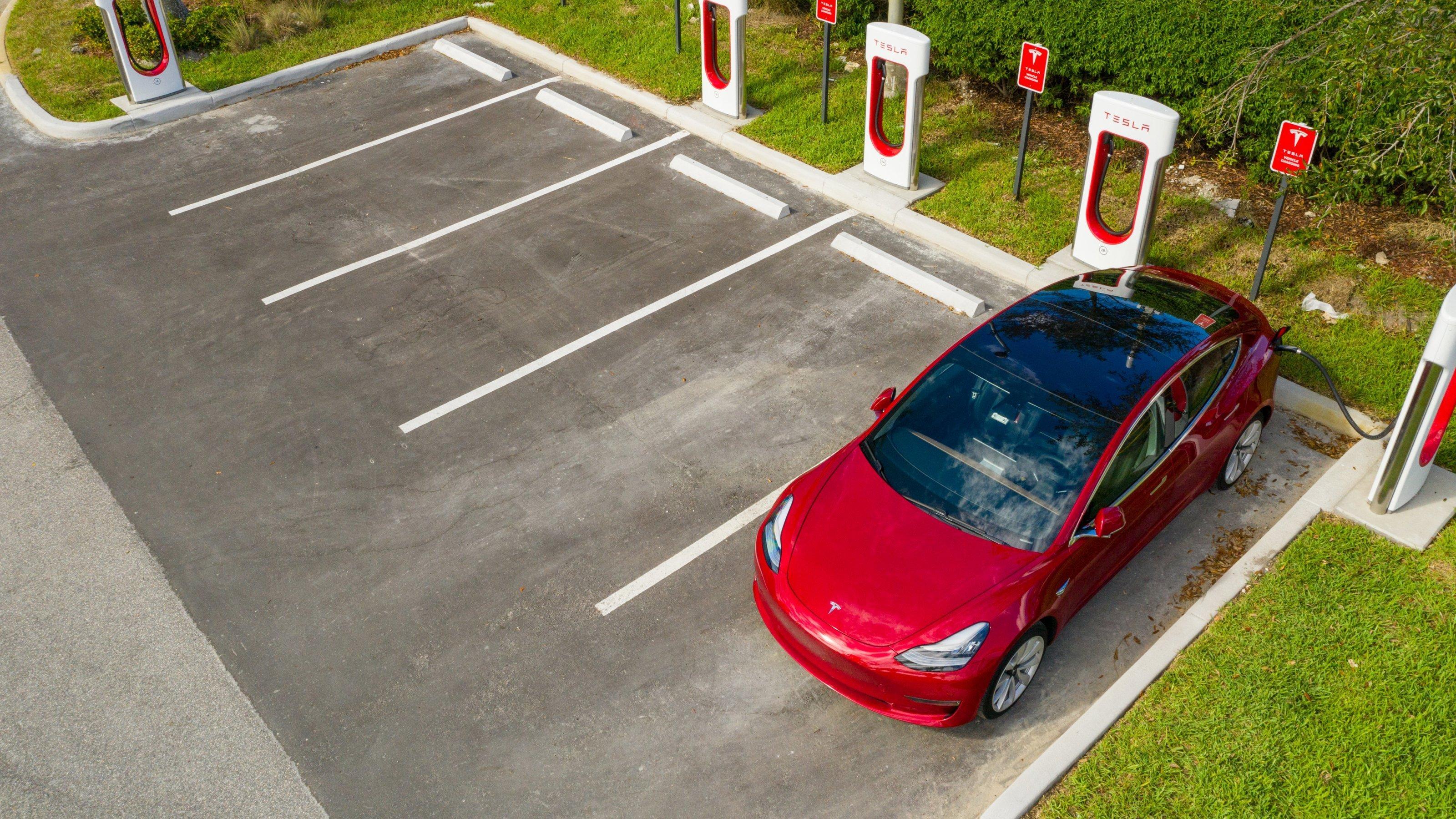 Luftbild eines roten Elektroautos, das an einer Tesla-Ladesäule hängt.