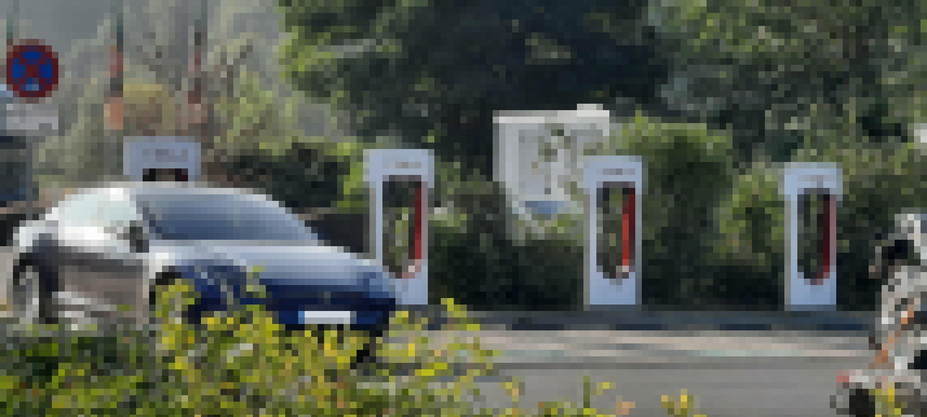 Ein Elektroauto ist an einer Ladesäule angeschlossen. Nebenan befinden sich weitere Parkplätze mit Ladesäulen, die aber nicht belegt sind.