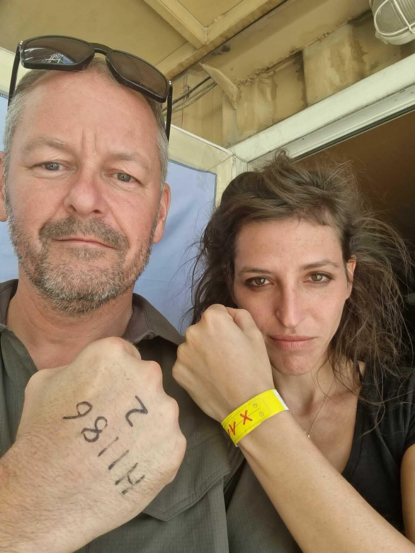 Rob Grey und Theresa Breuer halten beide ihre Handgelenke hoch. Grey hat das britische Evakuierungskennzeichen auf dem Handrücken stehen, Breuer das deutsche auf einem gelben Armband.