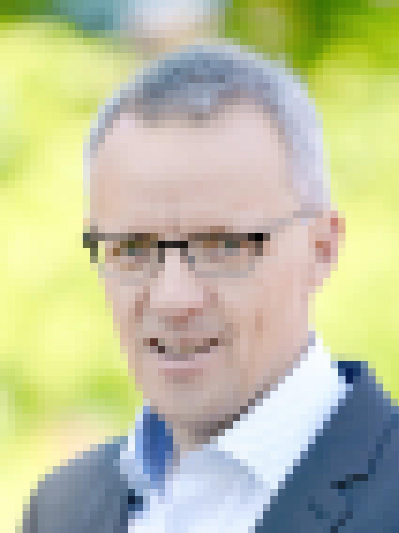 Ein Mann mit kurzen grauen Haaren und Brille schaut in die Kamera.