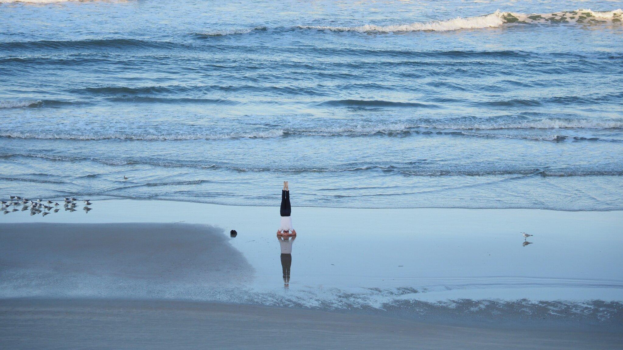 Das Meer, ein Mann am Strand, der einen Kopfstand macht.