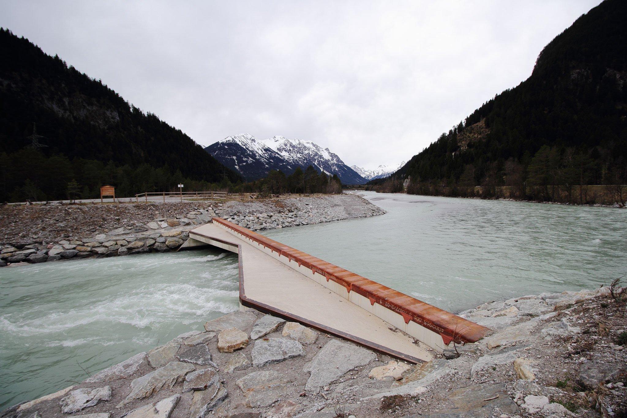 Betonierter Durchlass am Fluss, der Wasser und Schotter-Zufluss reguliert.