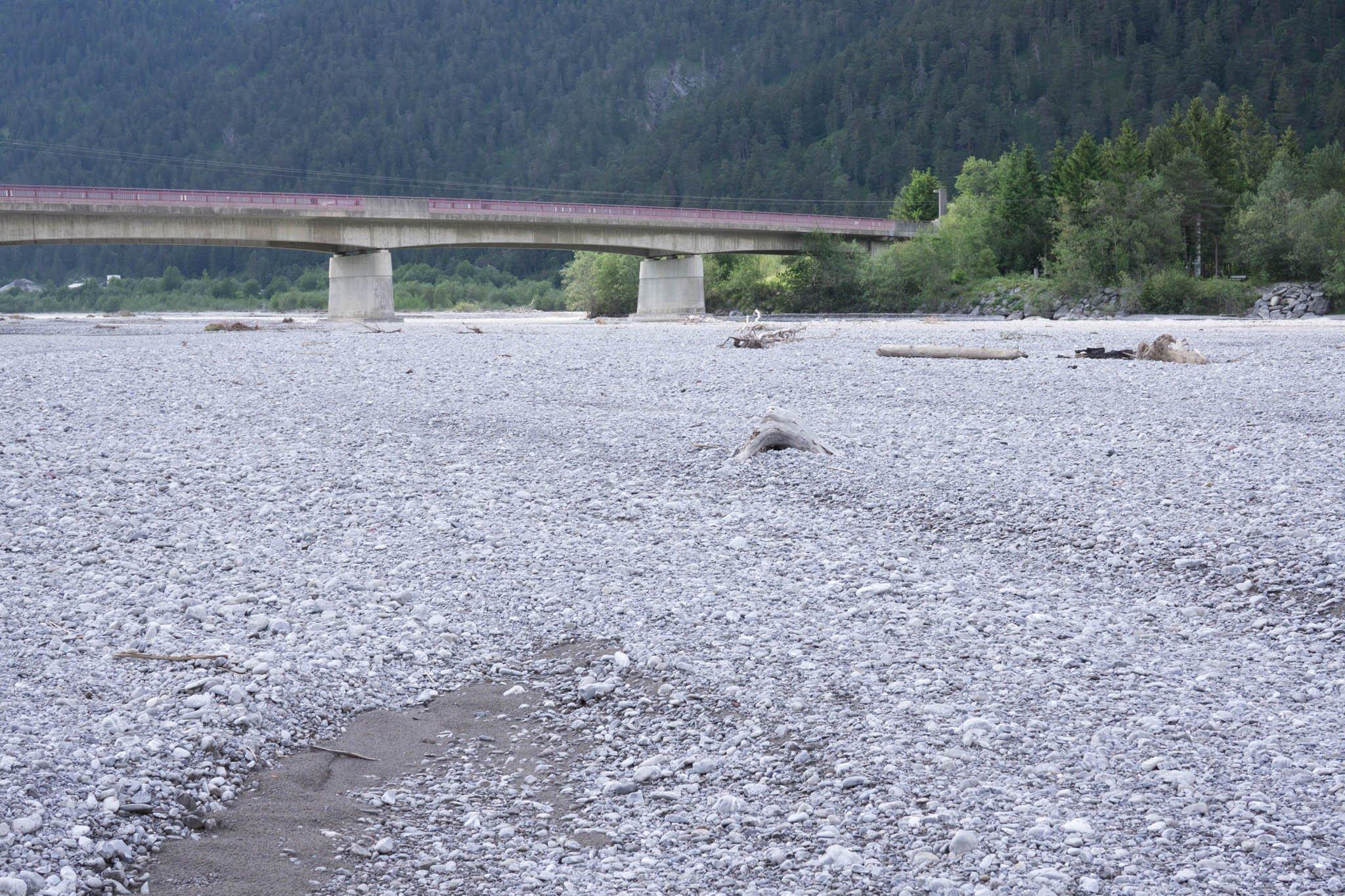 Große Schotterfläche mit Totholz, dahinter die Brücke.