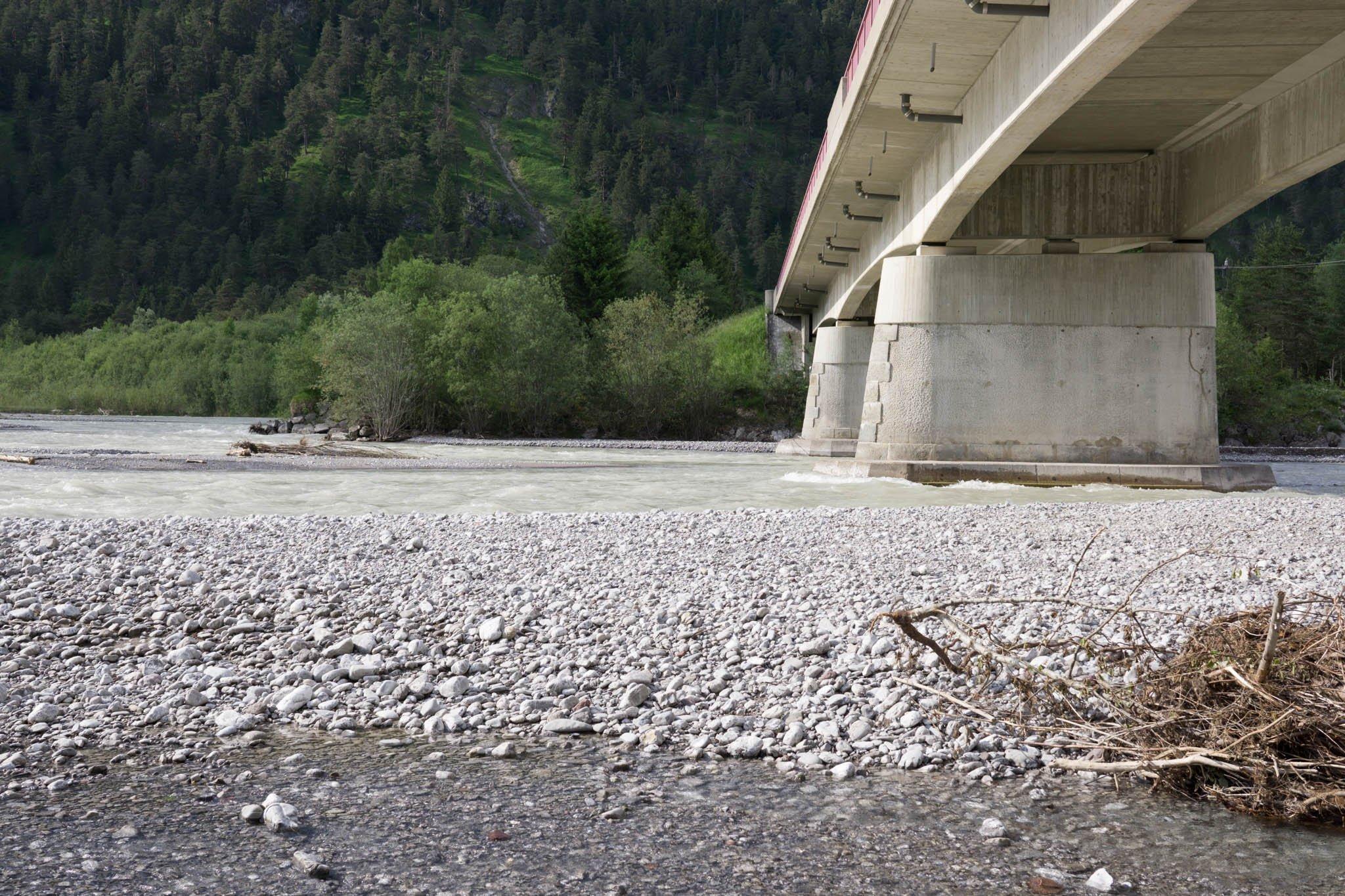 Brücke vom Flussufer aus gesehen mit Schotterbank.