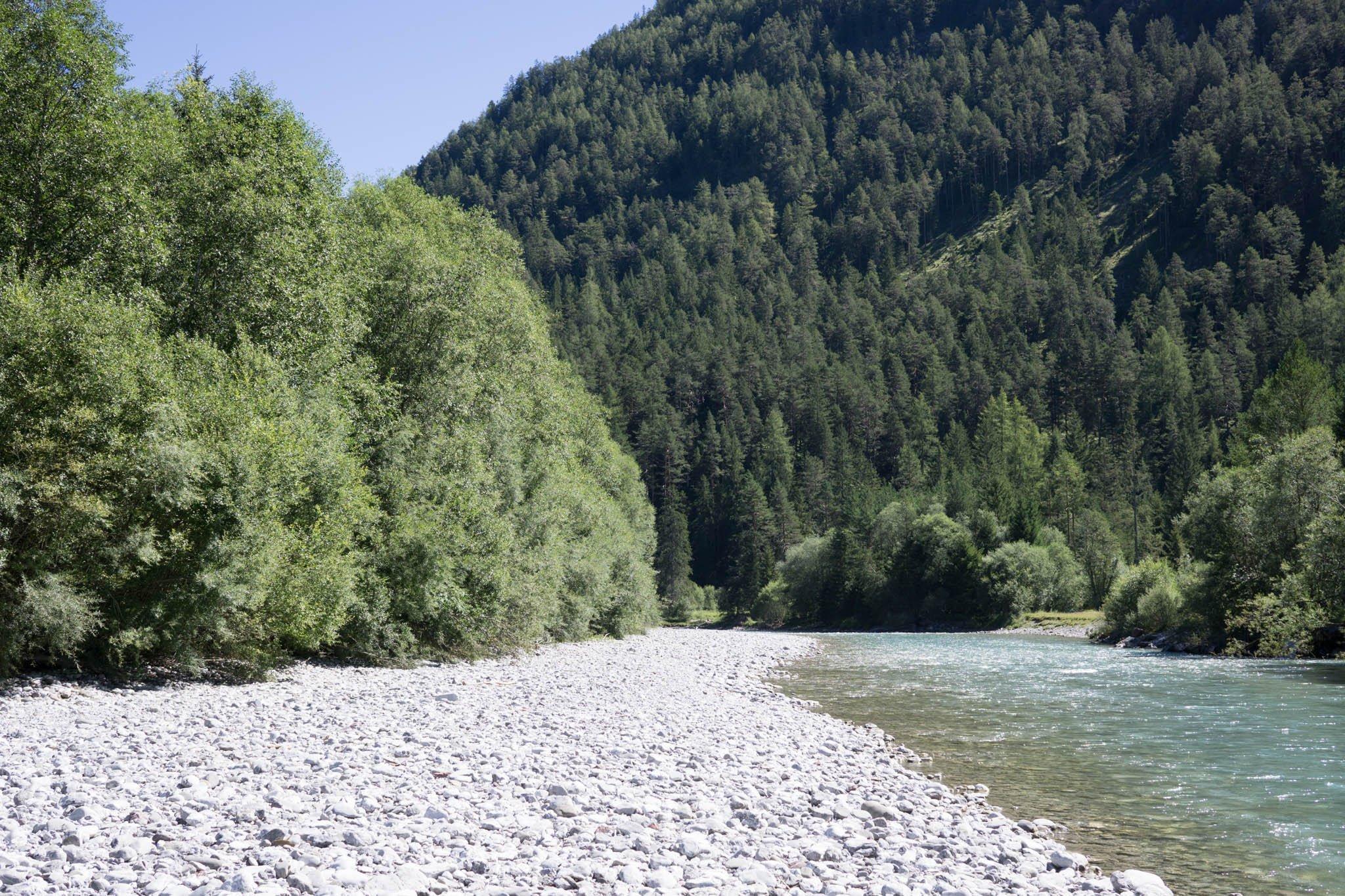 Links Bäume und Schotterbank, rechts Fluss, hinten ein Berg.