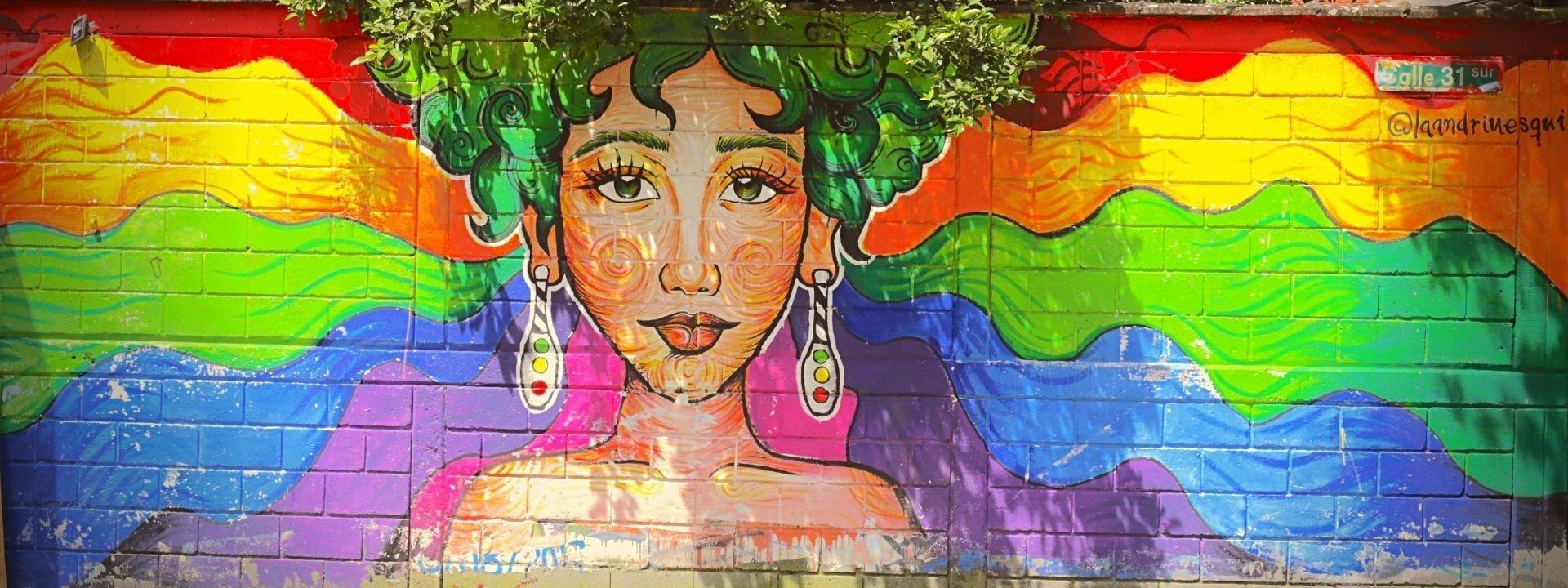 Das Foto zeigt eine Mauer mit einem gemalten Frauenkopf. Die Frau hat grüne Haare. Wo die Haare der Frau auf der Mauer enden, gehen sie in die Krone eines Baumes über, der hinter der Mauer steht. Die Frau sieht aus, als ob sie einen riesigen grünen Baum-Afro trüge.