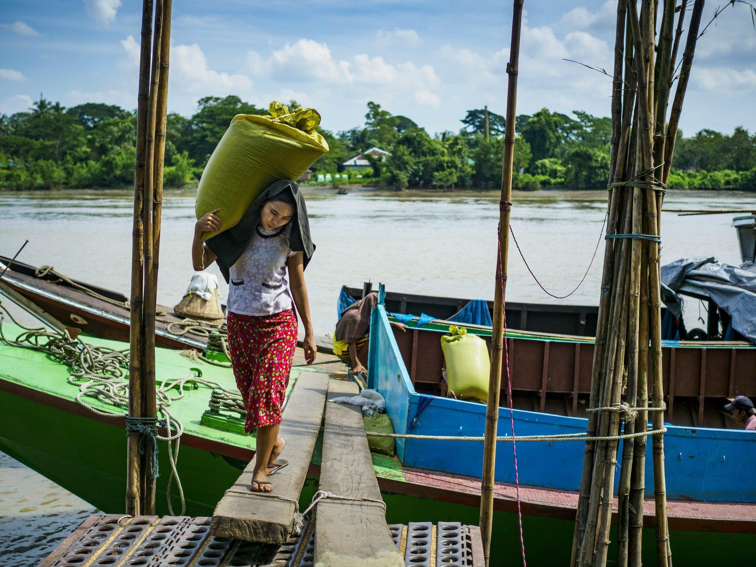 Eine Frau trägt einen Sack Reis von einem Boot am Irawadi-Fluss.