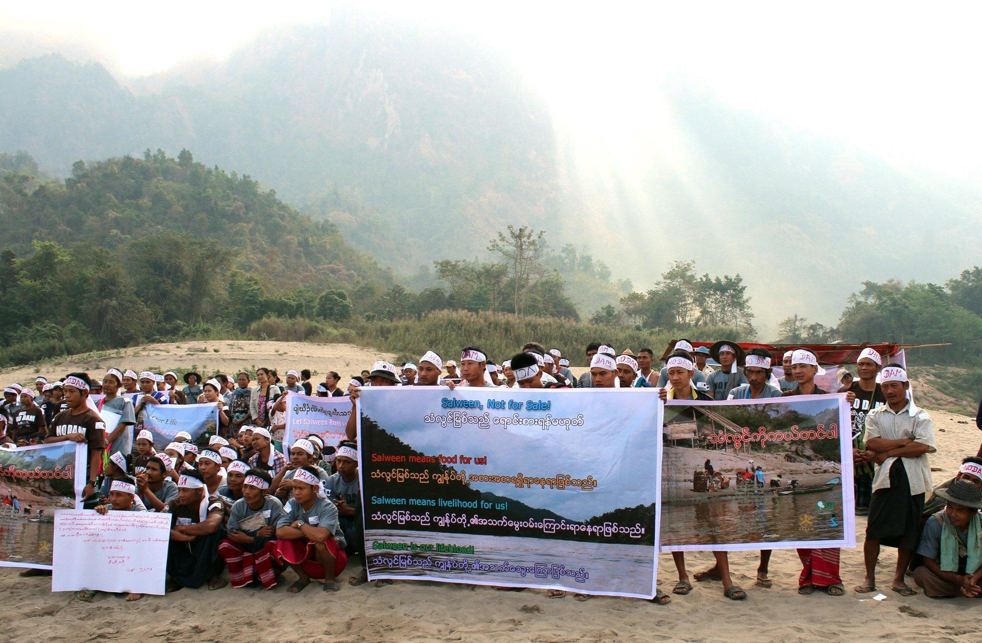 Menschen mit weißen Protest-Bändern auf der Stirn und Plakaten am Flussufer.