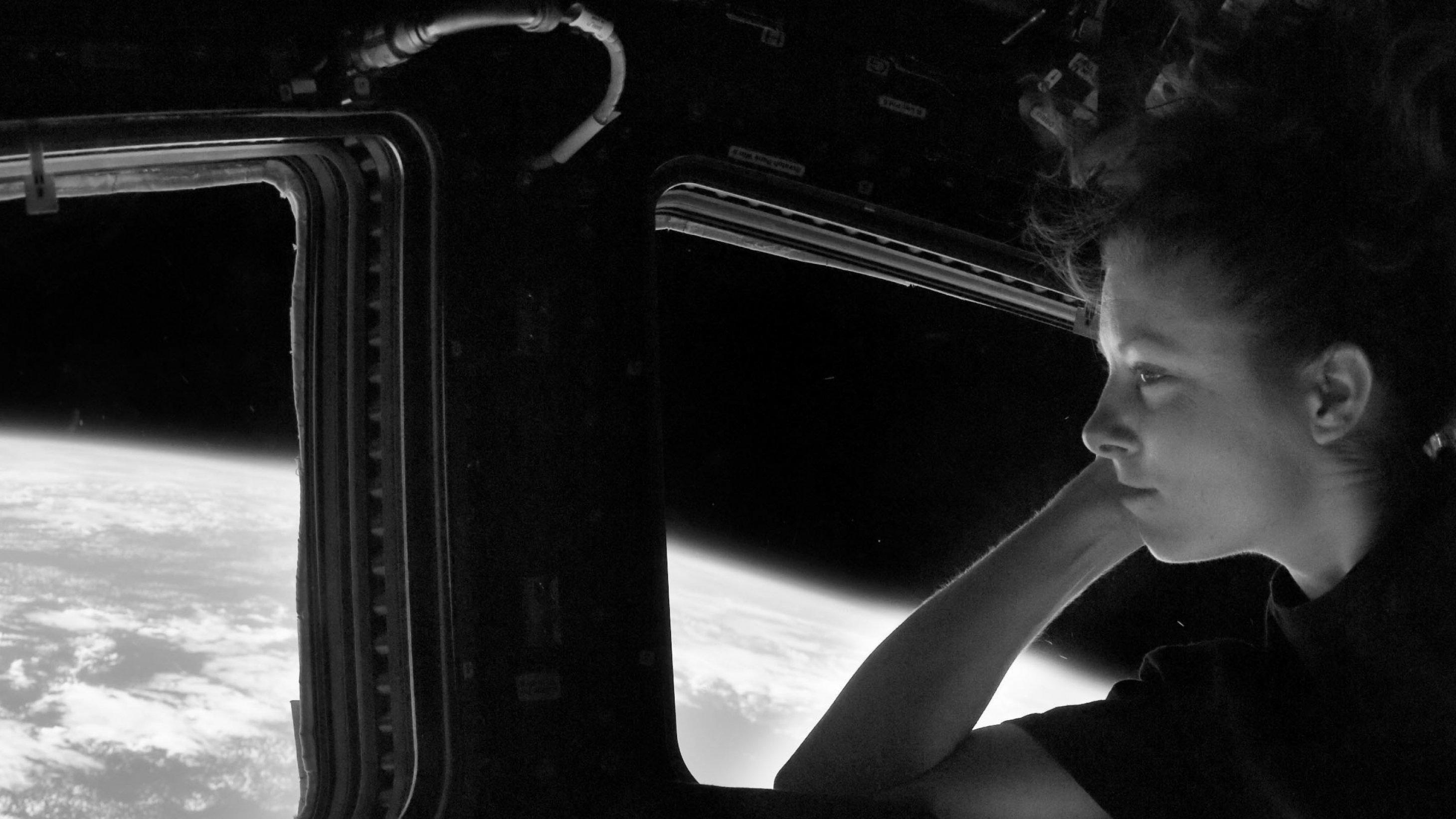 Eine NASA-Astronautin in schwarzem T-Shirt schaut aus einem Fenster der Raumstation und tut so, als würde sie ihren Kopf auf den Arm aufstützen (es sieht sehr entspannt aus).