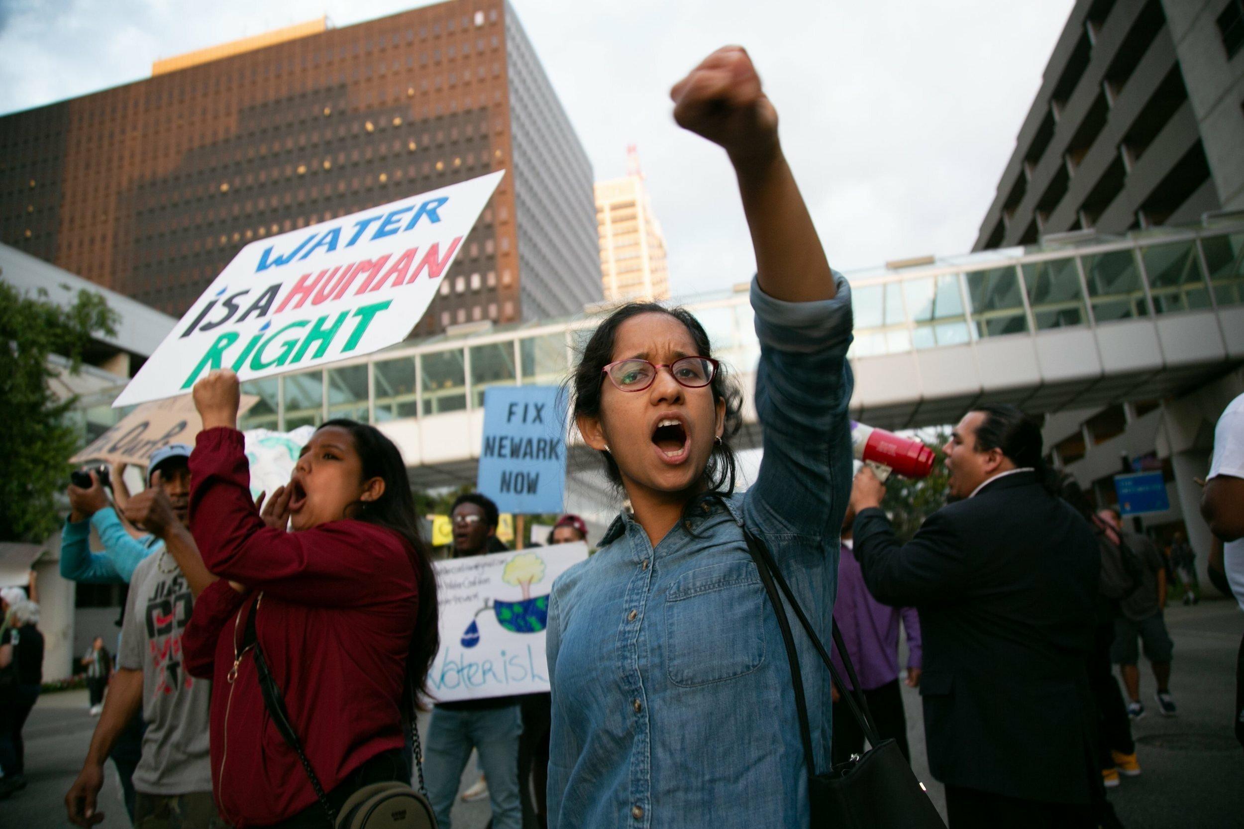 """Eine junge Demonstrantin reckt die Faust in die Höhe, während neben ihr eine Frau ein Schild mit der Aufschrift """"Water is a human right"""" in die Höhe hält."""