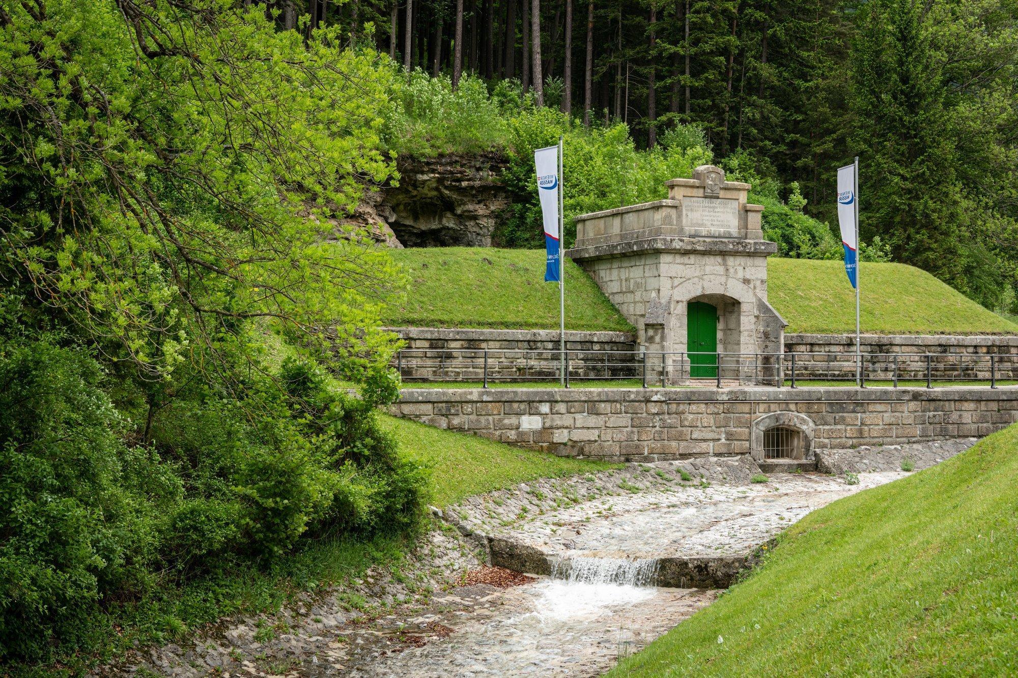 An einem bewaldeten Abhang befindet sich ein steinernes Tor in die Schächte der Wiener Wasserversorgung. Daneben stehen zwei Fahnen.