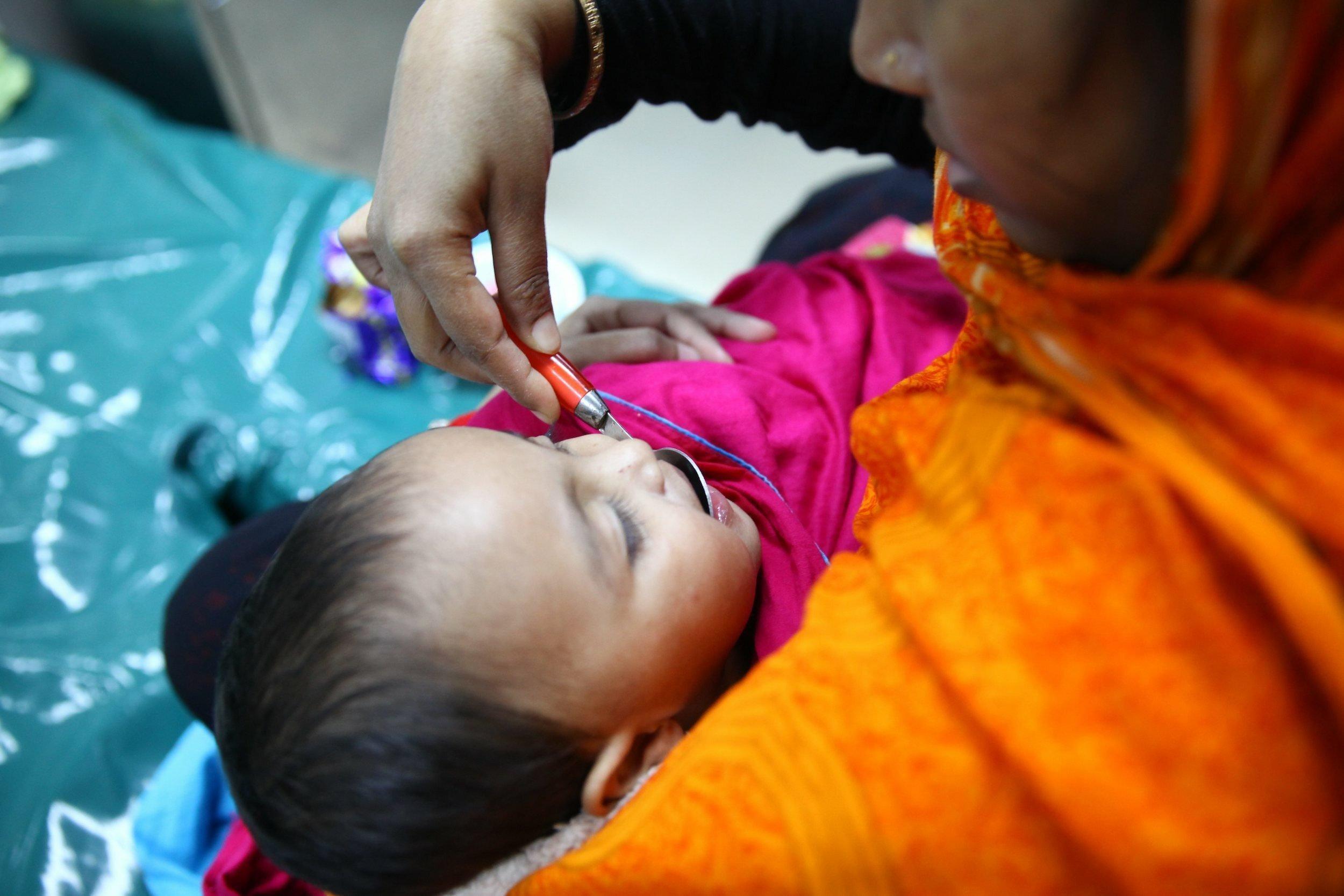 Eine Frau hat ein Baby im Arm und einen Löffel in der rechten Hand, den sie an den Mund des Kindes führt.