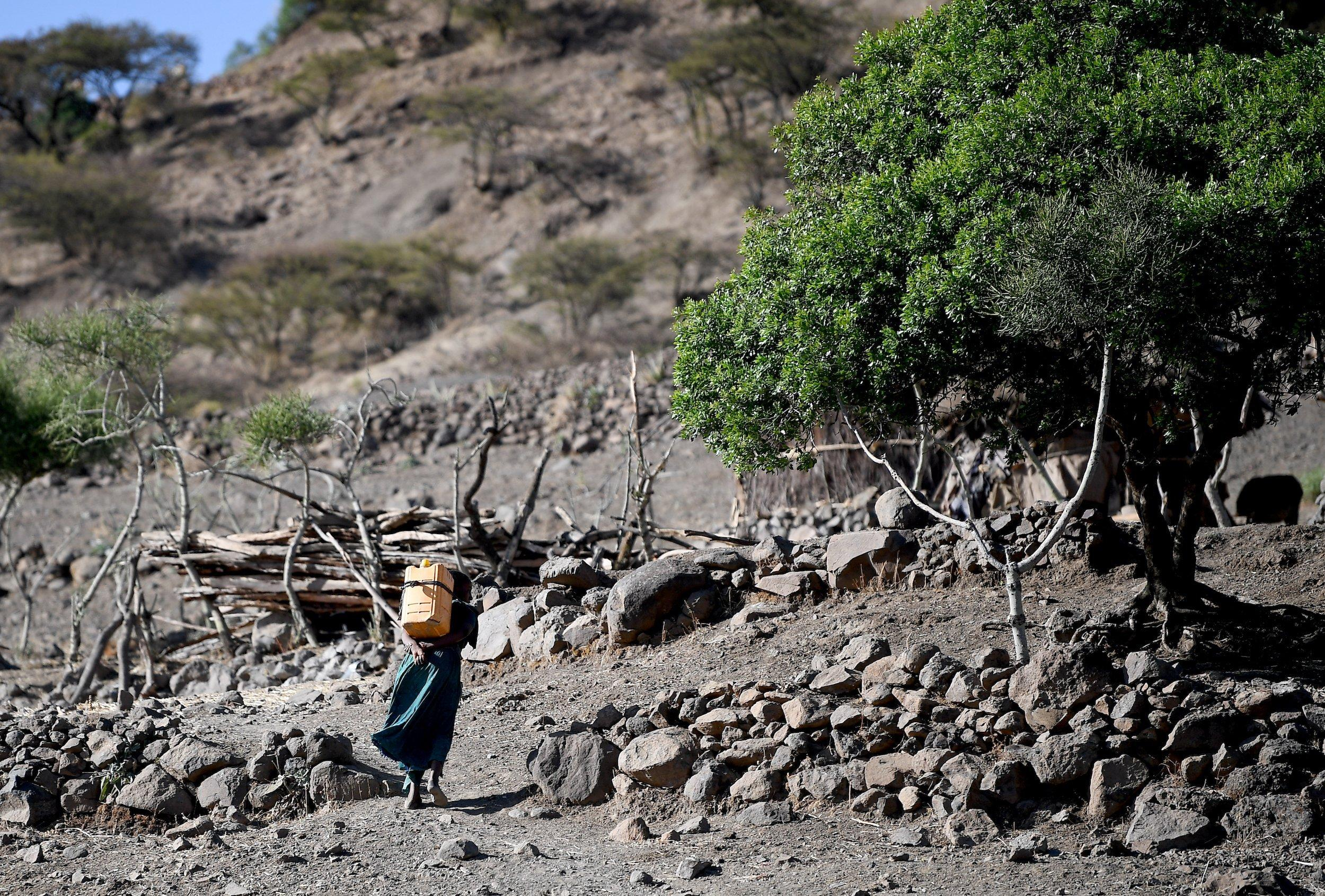 Lalibela, Äthiopien: Ein Mädchen trägt in einer ausgetrockneten Landschaft einen Kanister mit Wasser auf ihrem Rücken über ein Feld zu ihrem Zuhause.