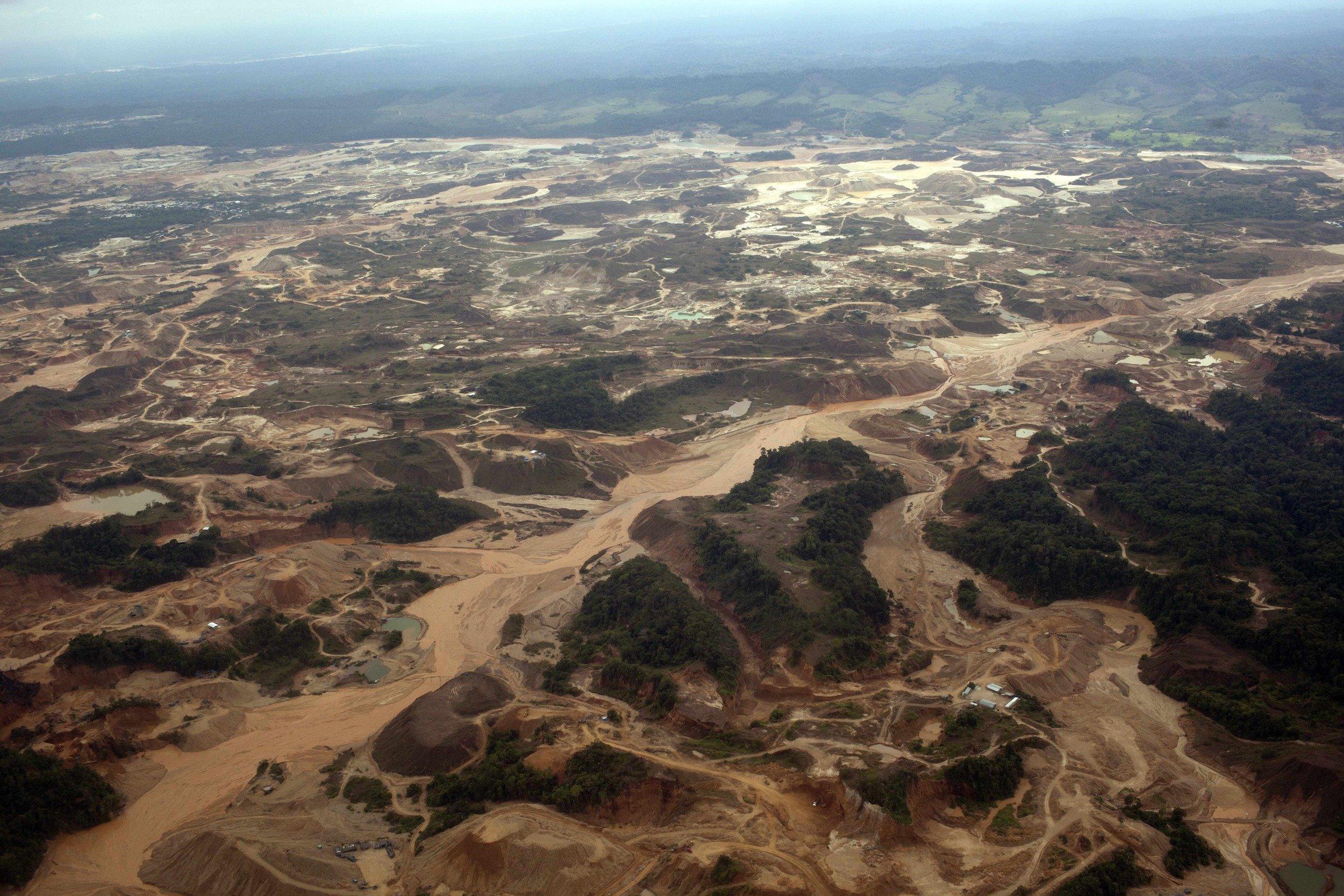 Luftaufnahme eines Bergbaugebiets. Die Oberfläche ist bis zum Horizont aufgerissen, trübe Abwässer gelangen in einen Fluss.