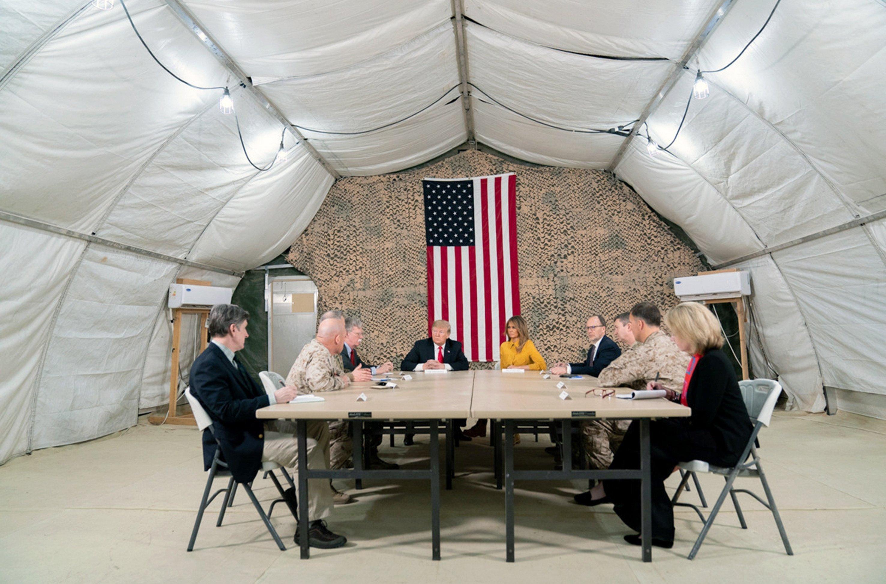 Mehrere Personen sitzen in einem Zelt. Im Hintergrund hängt die US-amerikanische Fahne.