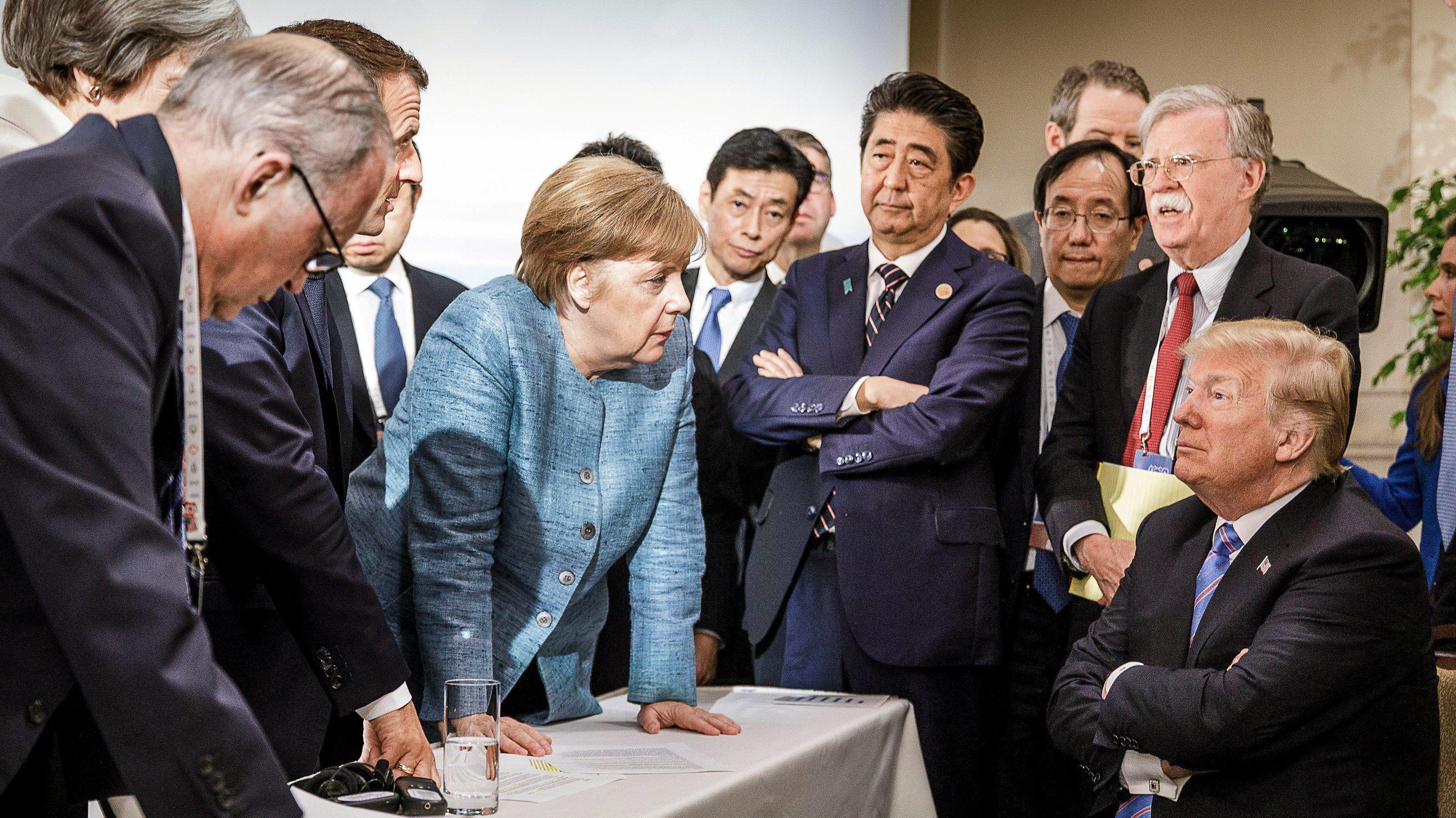 Mehrere ältere Männer und Herren stehen bzw. sitzen um einen Tisch herum und reden.