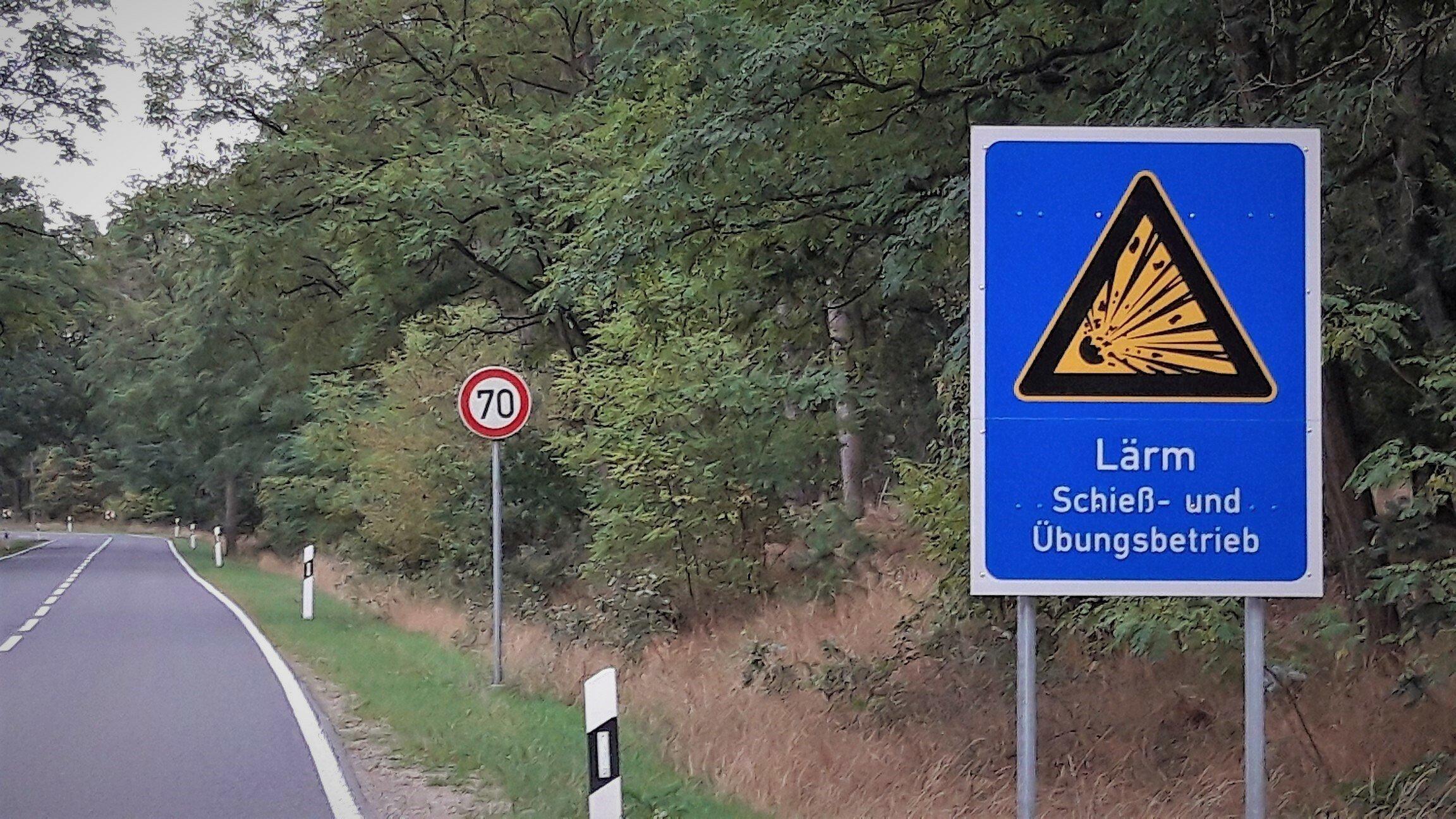"""Vor einer waldumsäumten Straße steht das blaue Warnschild mit der Aufschrift """"LÄRM – Schieß- und Übungsbetrieb""""."""