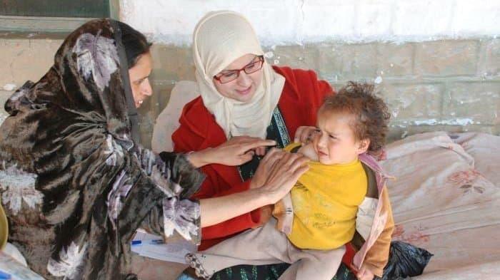 Eine Mutter hält ein Kleinkind in den Armen, eine Frau, eine Ärztin untersucht das Kind nach einer Impfung gegen Tuberkulose.