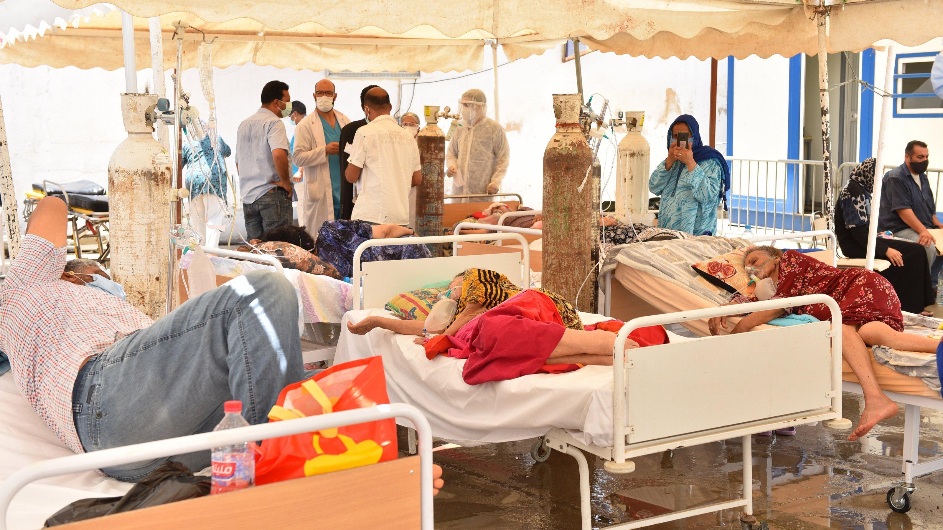 Erkrankte liegen an Sauerstoffflaschen unter einem improvisierten Zelt. Im Hintergrund diskutiert eine Gruppe von Ärztïnnen und Pflegekräften.