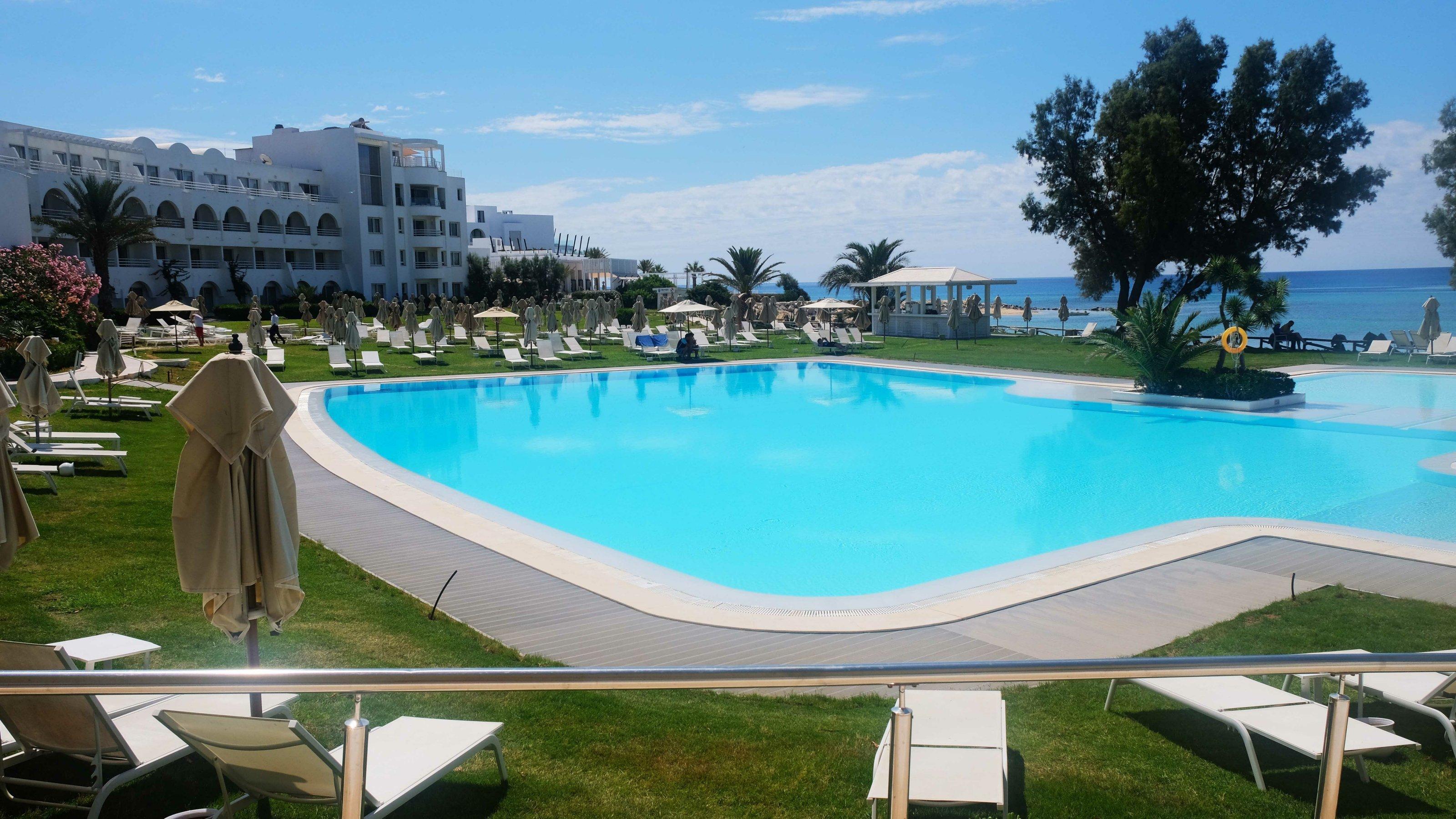 Blick auf Pool und leere Liegestühle auf einer Wiese im Hotel Sultan in Hammamet, Tunesien.