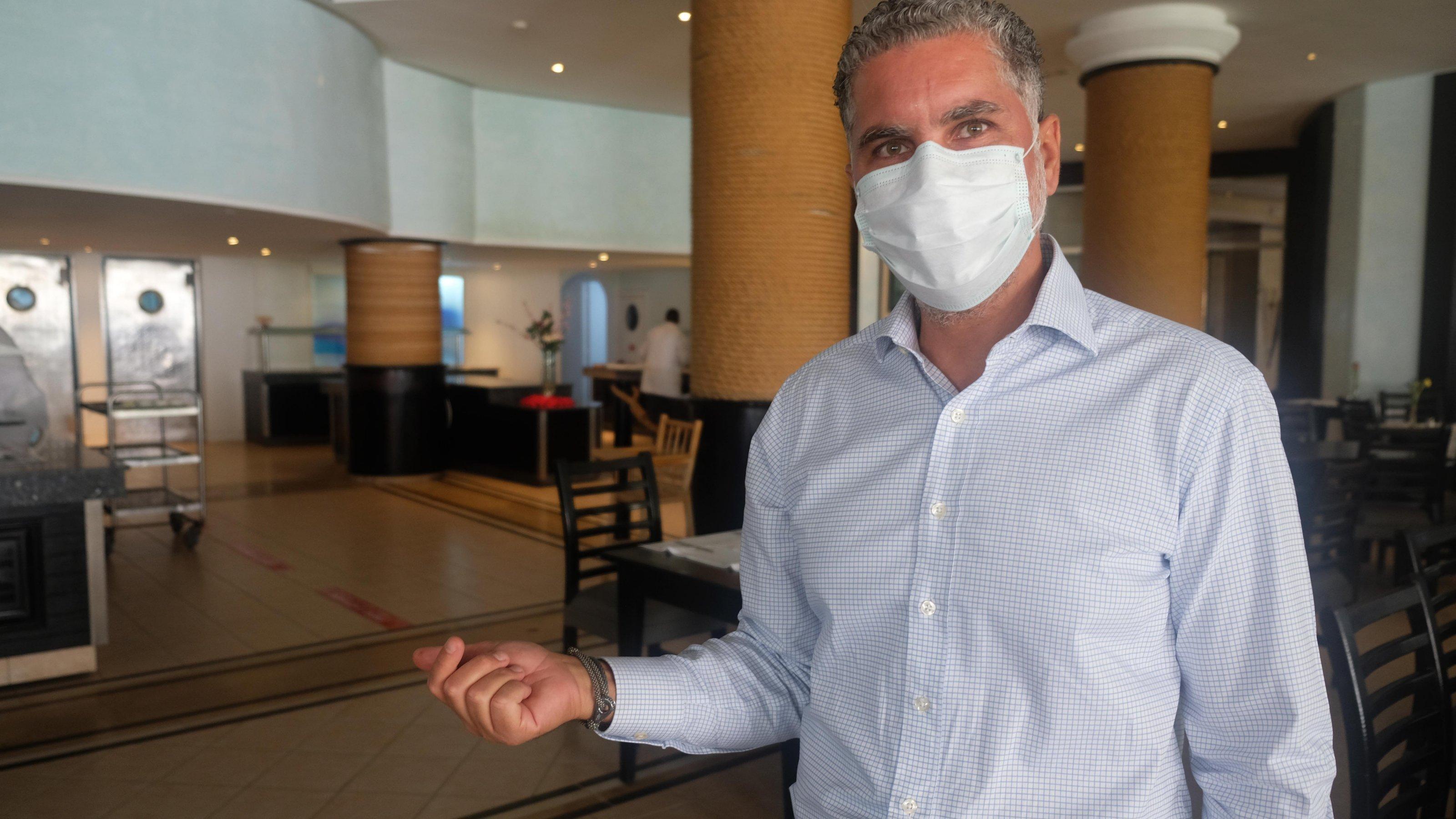 Ein Mann mit Gesichtsmaske steht im Hotelrestaurant.