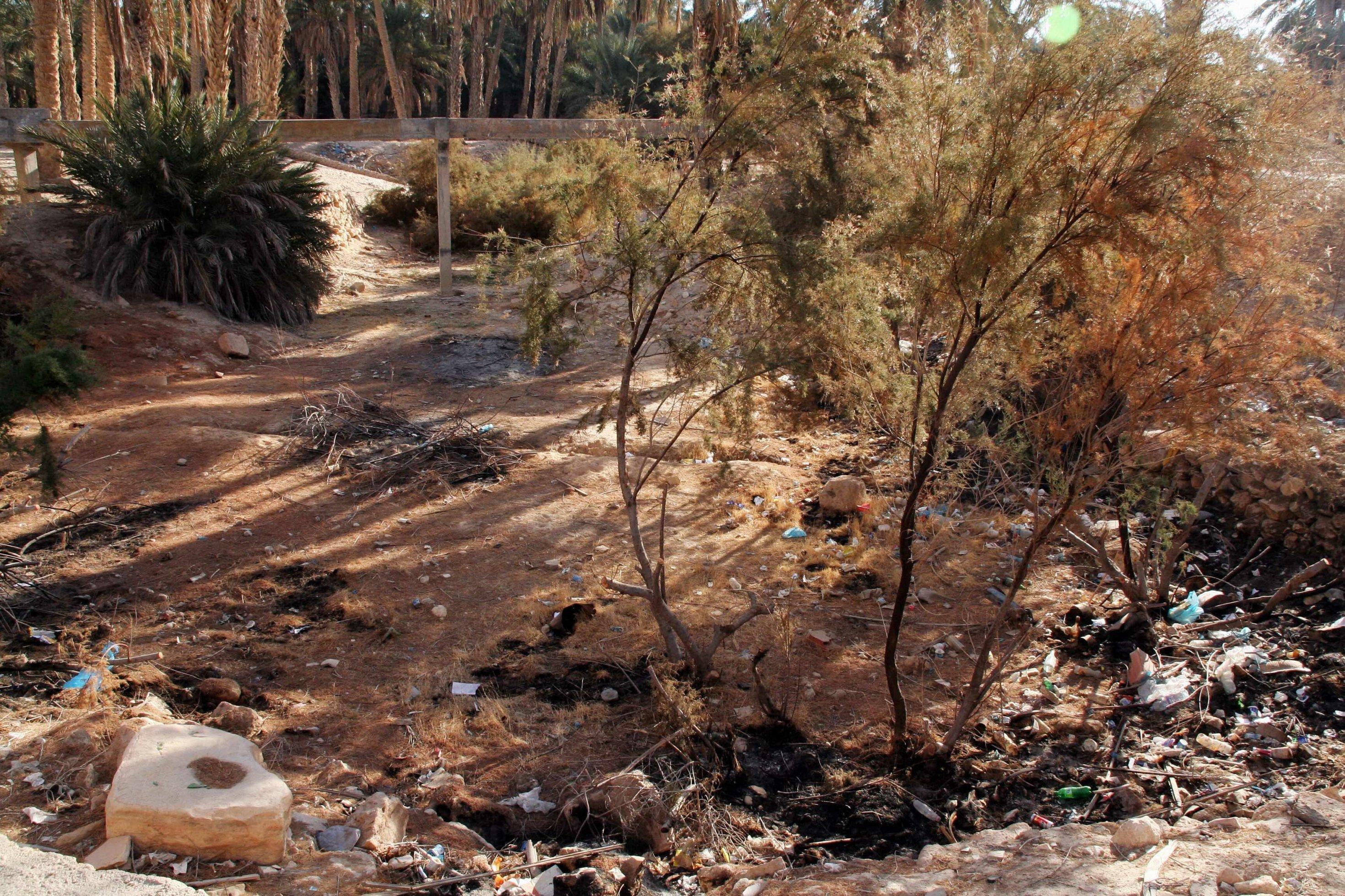 Ein trockenes Flussbett ist mit Müll übersäht.