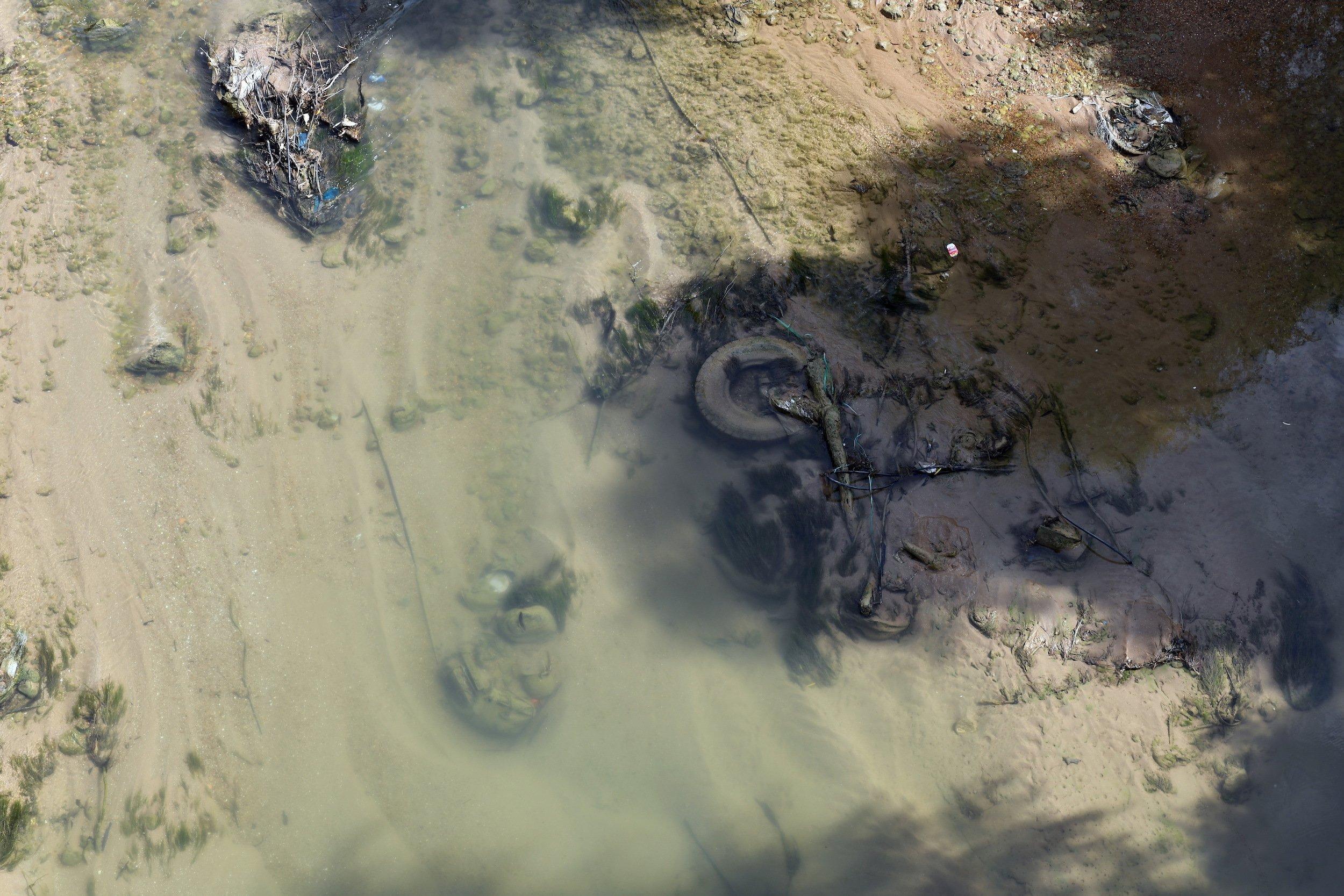 Von Algen überwucherter Autoreifen im Flussbett