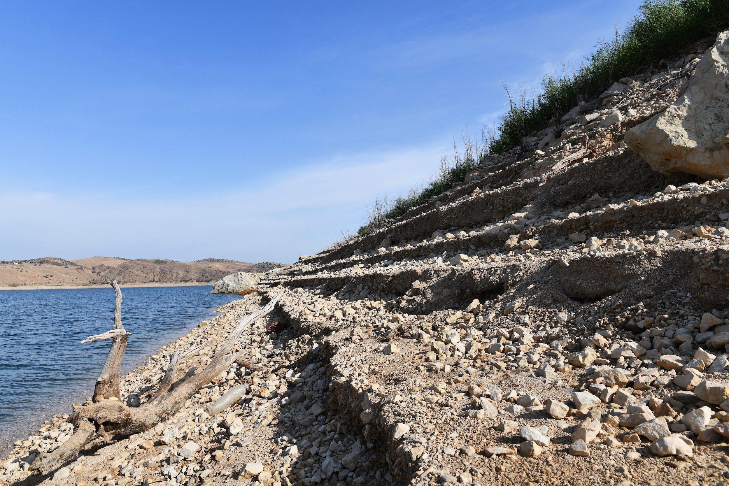 Am Rand des Staudamms sind im Geröll Stufen von vorherigen Wasserständen zu sehen.