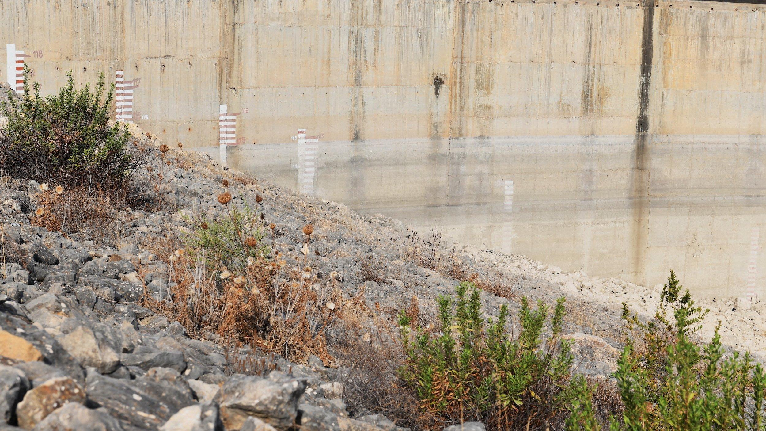 An der Mauer eines Staudamms sind die Spuren des Wasserstands vergangener Jahre und verblichene Höhenangaben zu sehen. Im Vordergrund wachsen Büsche auf Kies.