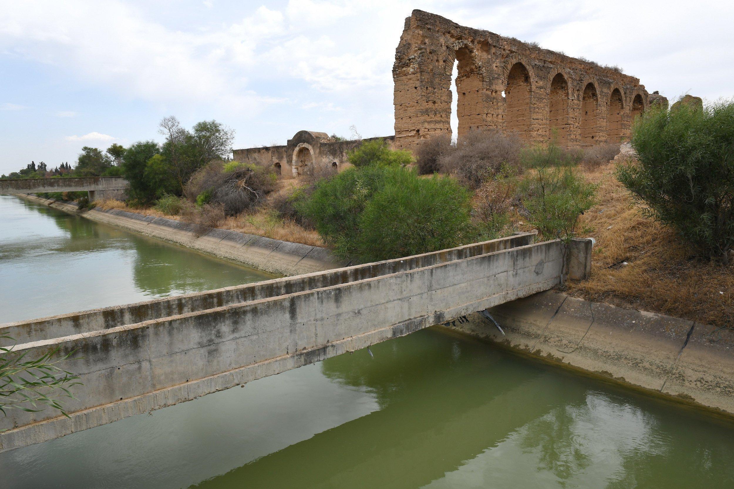 Im Hintergrund sind Ruinen eines römischen Aquädukts zu sehen, im Vordergrund der verschmutze Kanal Medjerda – Cap Bon