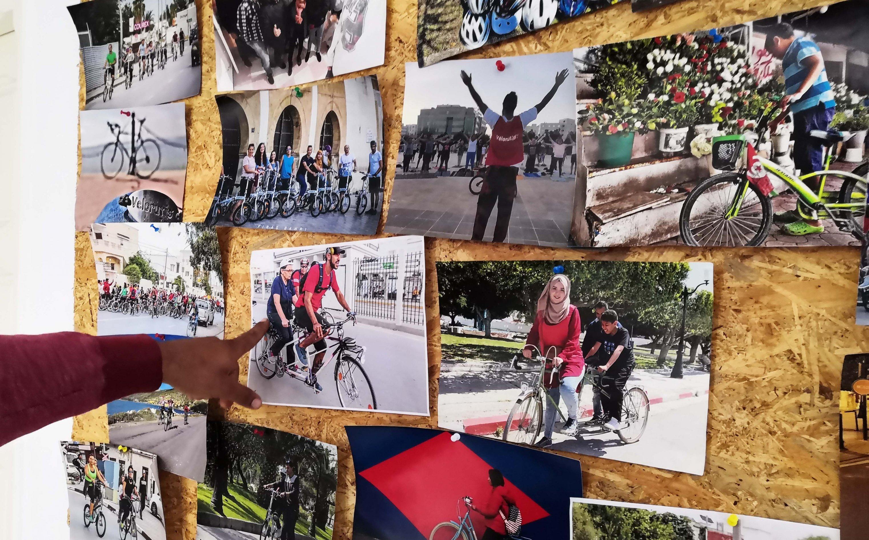 Oussama Tangara vor einer Pinnwand mit Bildern der verschiedenen Aktionen des Vereins