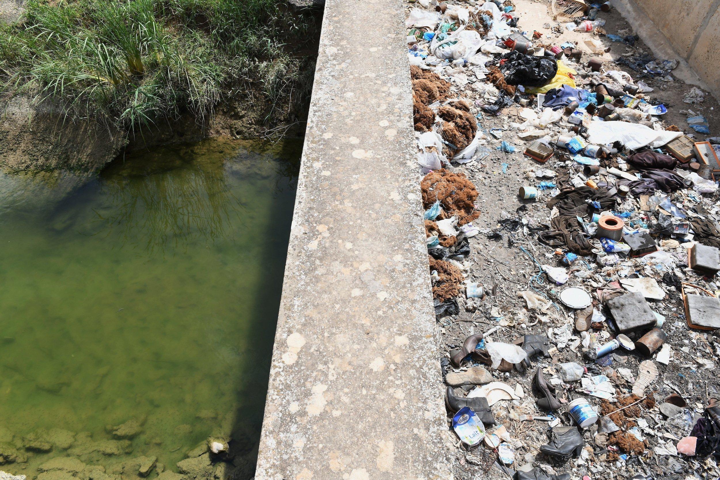 Trübes Wasser in einem Kanal, über den eine mit Müll überfüllte Brücke führt