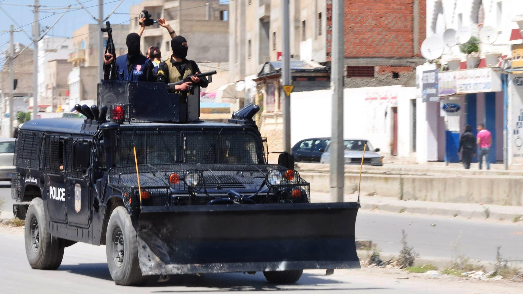 Polizei-Fahrzeug, von dem zwei schwerbewaffnete Polizisten runterschauen.