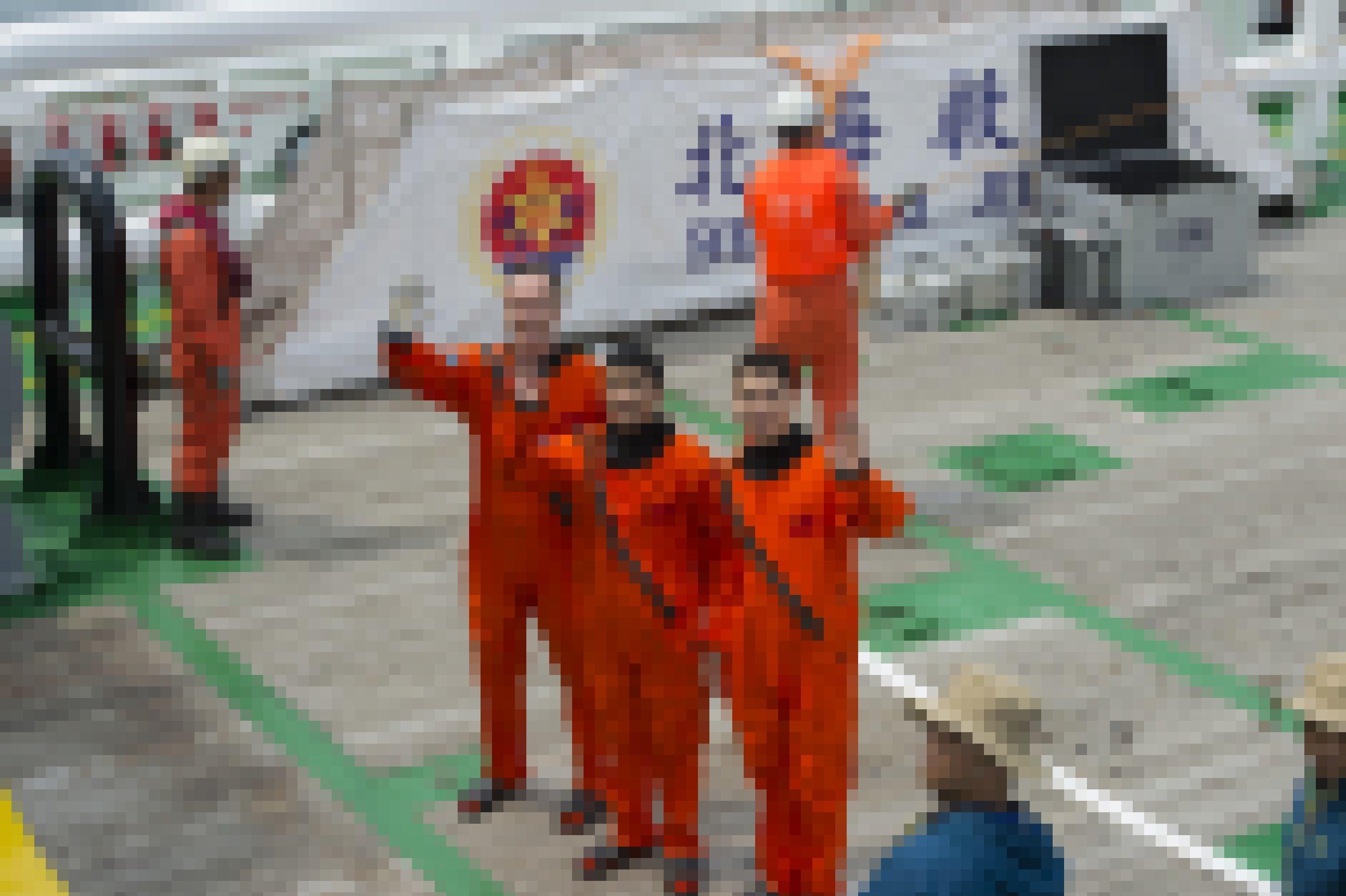 Drei Raumfahrer mit Matthias Maurer stehen in orangenen Overalls an Deck eines größeren Schiffs und winken
