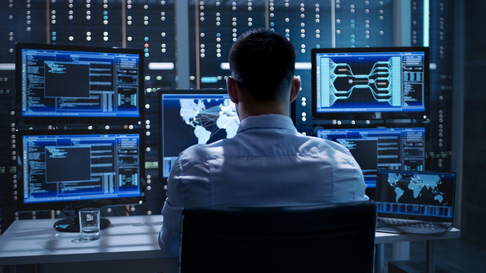 Ein Mann sitzt in einem Büro vor vielen Bildschirmen, die blau leuchten