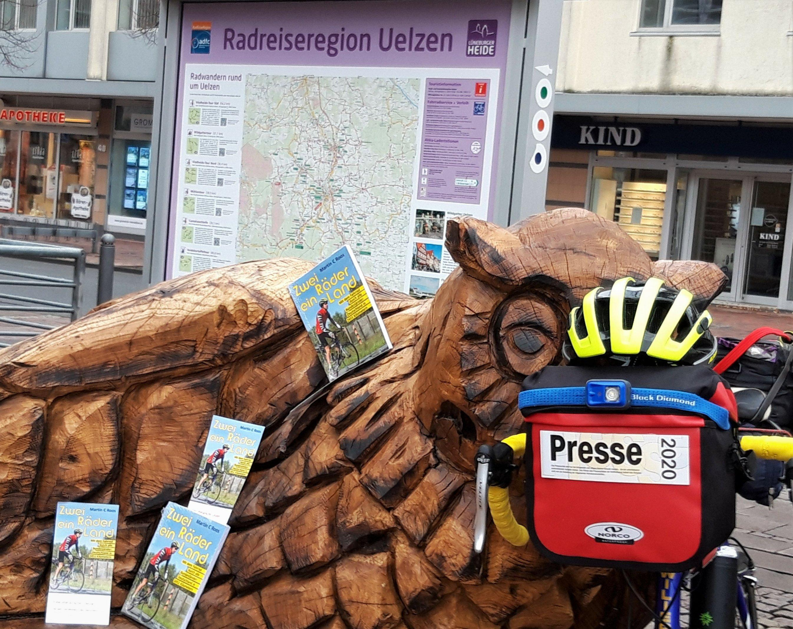 """Vor einer Tafel mit der Aufschrift """"Radreiseregion Uelzen"""" sind die Flyer des Buchs """"Zwei Räder, ein Land"""" auf einer Holzbank verteilt."""