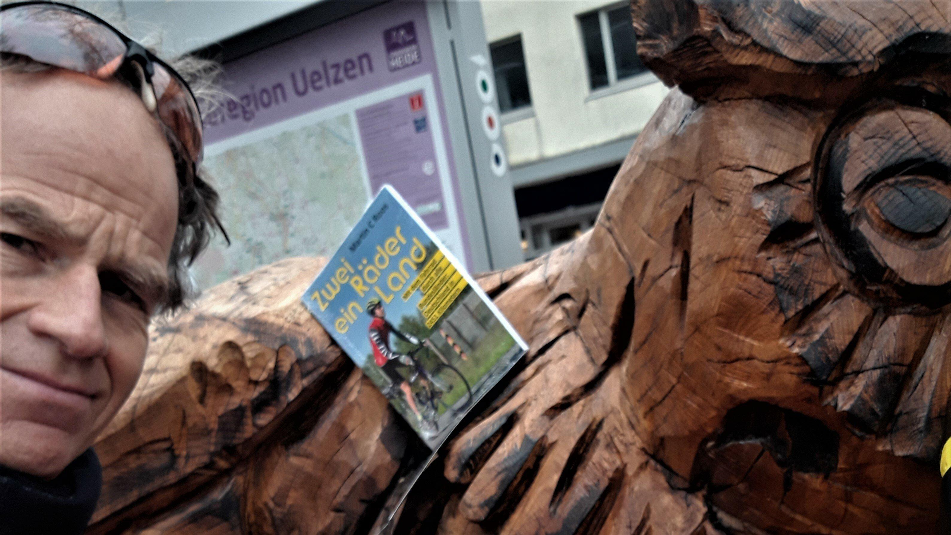 """Der RadelndeReporter rastet an der riesigen Eulen-Bank mitten in Uelzen, geschaffen vom Motorsägenkünstler Andrée Löbnitz, um sein Buch """"Zwei Räder, ein Land"""" der Öffentlichkeit zu präsentieren."""
