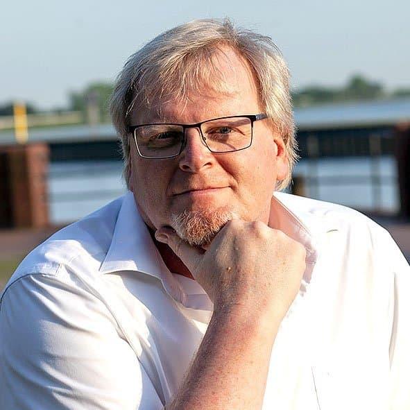Ulf Buschmann, ein Mann mit Brille stützt seinen Kopf auf eine Hand und schaut in die Kamera