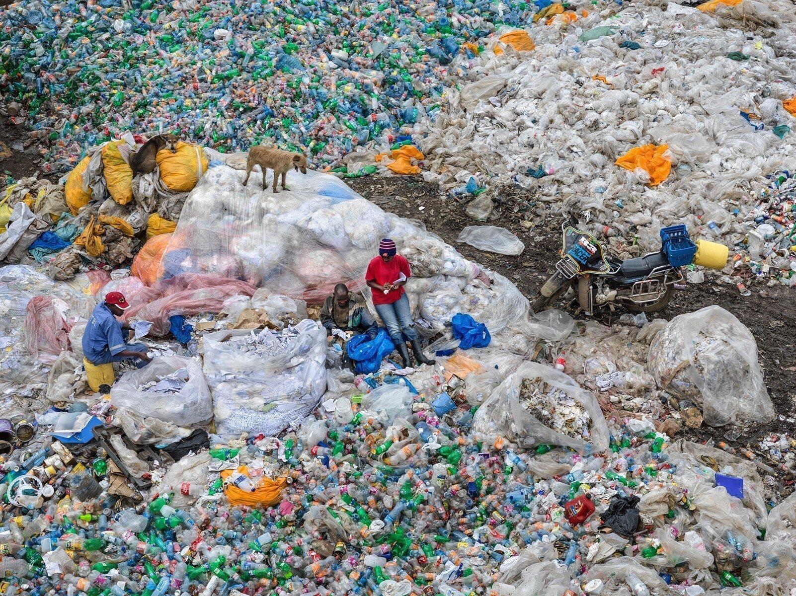 Das Bild zeigt zwei Männer inmitten einer Plastikmüll-Deponie in Kenia.