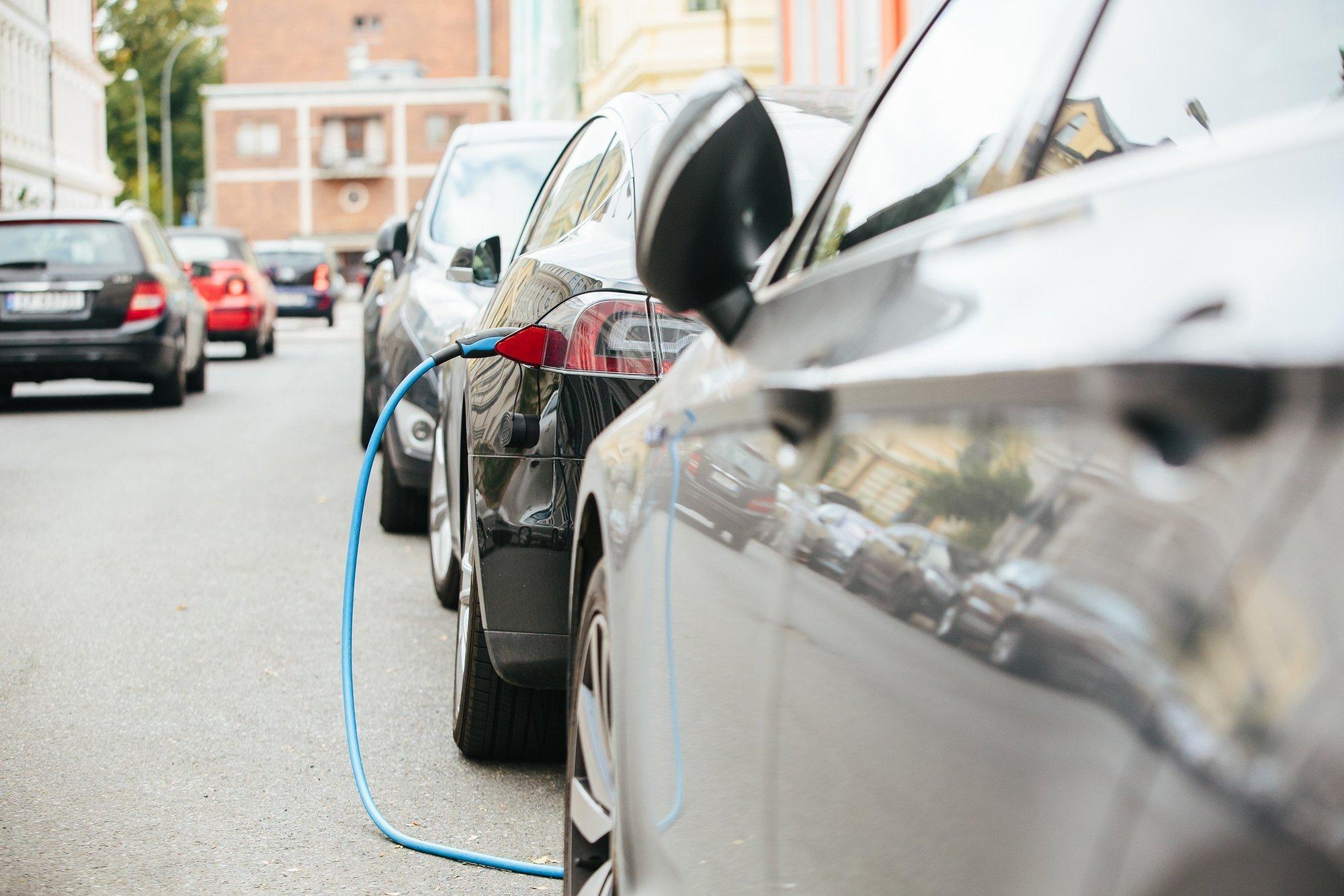 Das Bild zeigt eine Straße voll mit fahrenden und parkenden Autos, von denen eines ein Elektroauto ist und am Straßenrand mit einem Stromkabel neu aufgeladen wird.