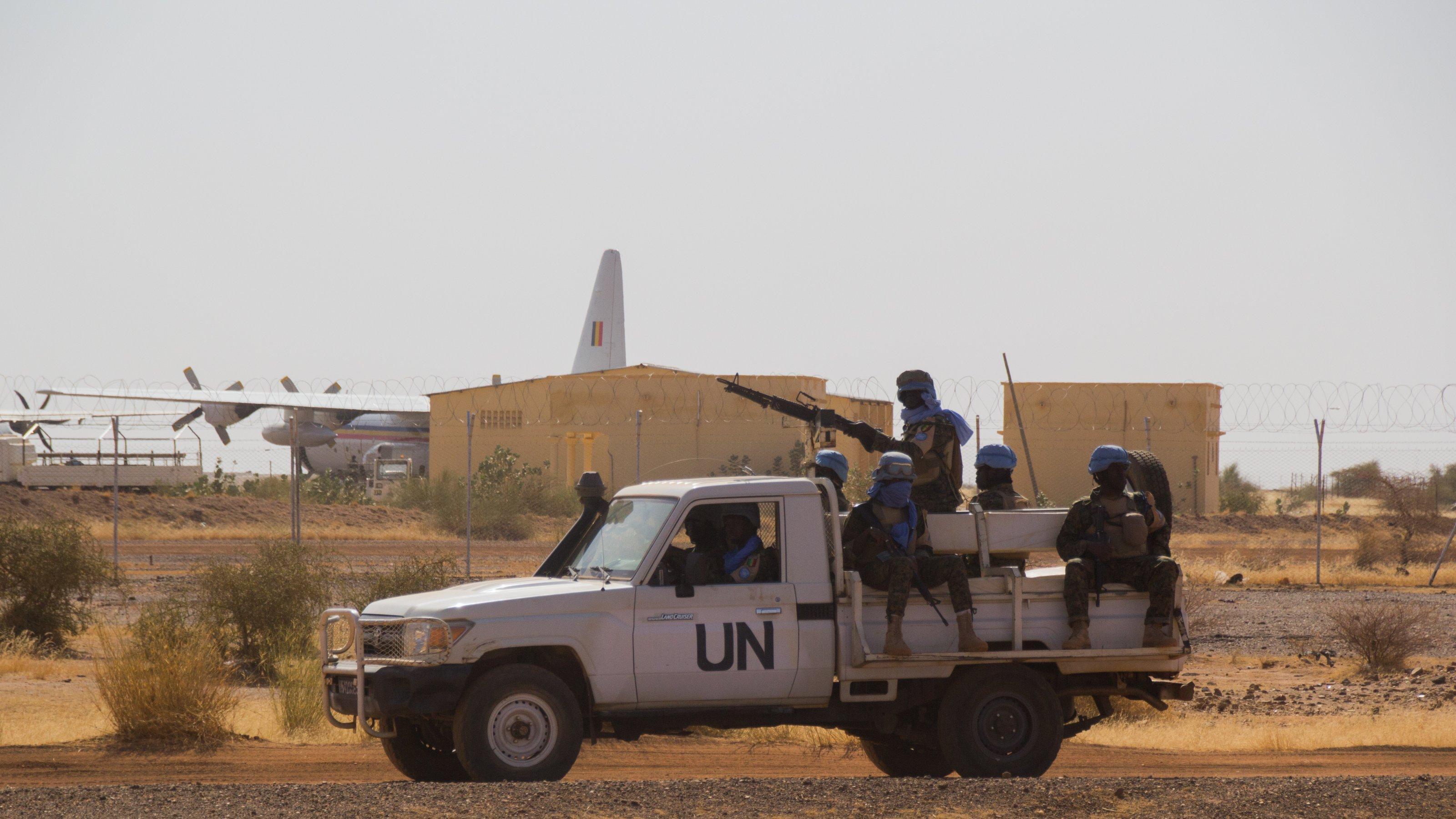 Man sieht einen Pickup mit aufmontiertem Geschütz, auf den Bänken darum herum sitzen Blauhelm-Soldaten. Die Luft ist staubig, die Erde trocken. Im Hintergrund ist ein Flughafen zu sehen, eine Maschine zu einem guten Teil hinter dem Flughafengebäude verborgen.