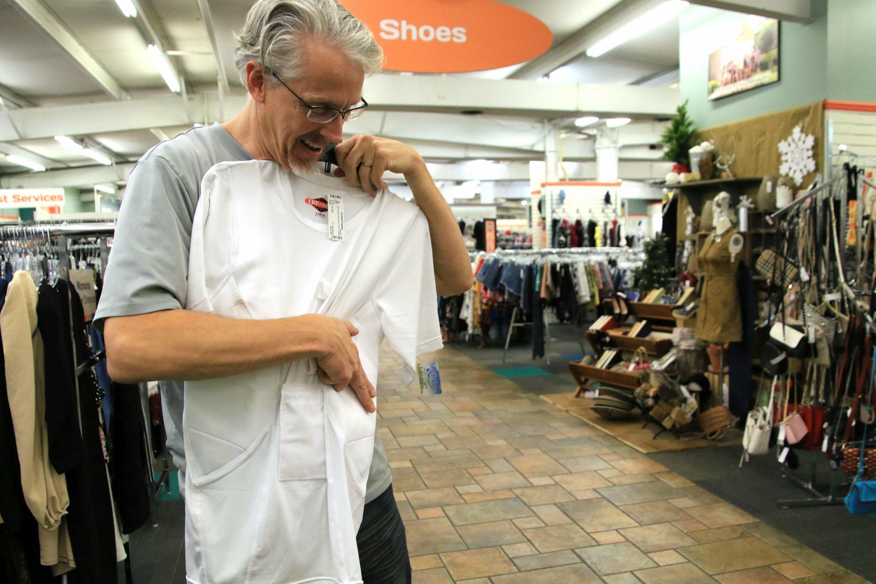 Ein grauhaariger Mann betrachtet ein Unterhemd in einem Supermarkt.