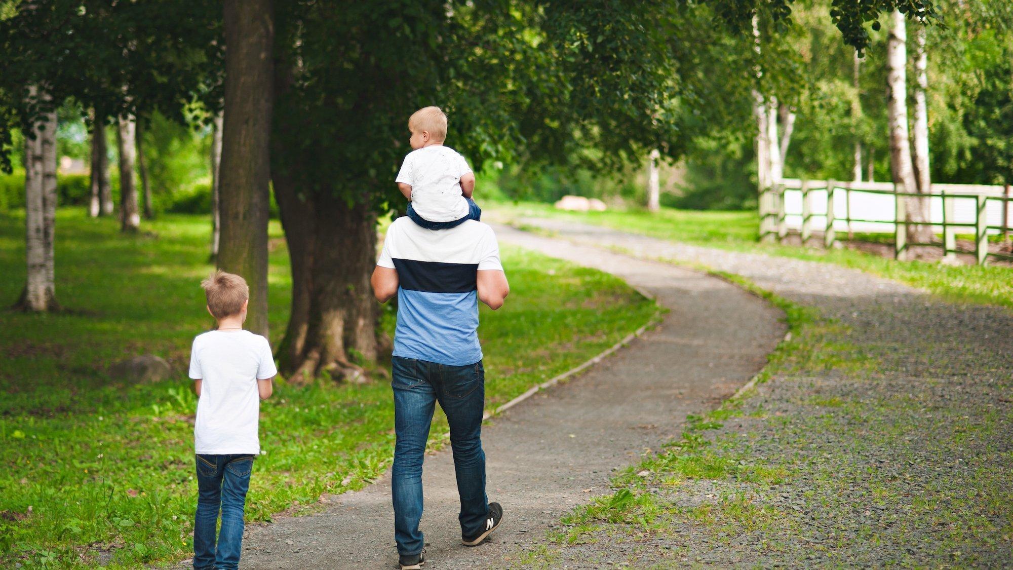Dargestellt ist ein Mann, der ein kleines Kind auf den Schultern trägt. Ein zweites Kind läuft knapp hinter ihm. Das Bild symbolisiert einen Vater, der sich Zeit für seine Kinder nimmt.