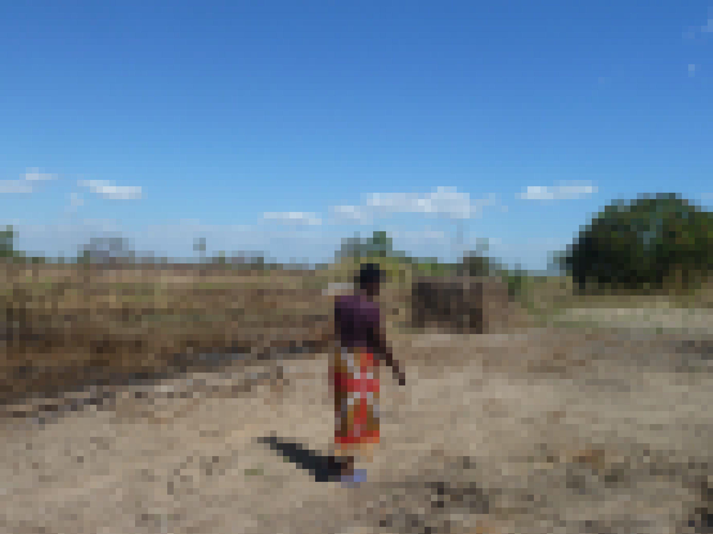 Das Bild zeigt eine Kleinbaeuerin in Mosambik, die an ihrem Feld vorbeigeht – Zyklon Idai hat es 2019komplett vernichtet. An einen Anbau ist nicht zu denken