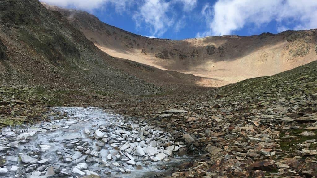 Über einem weiß schimmernden Bachlauf zieht sich eine gletscherlose Wüste aus grauen und braunen Steinen hinauf in den blauen Himmel.
