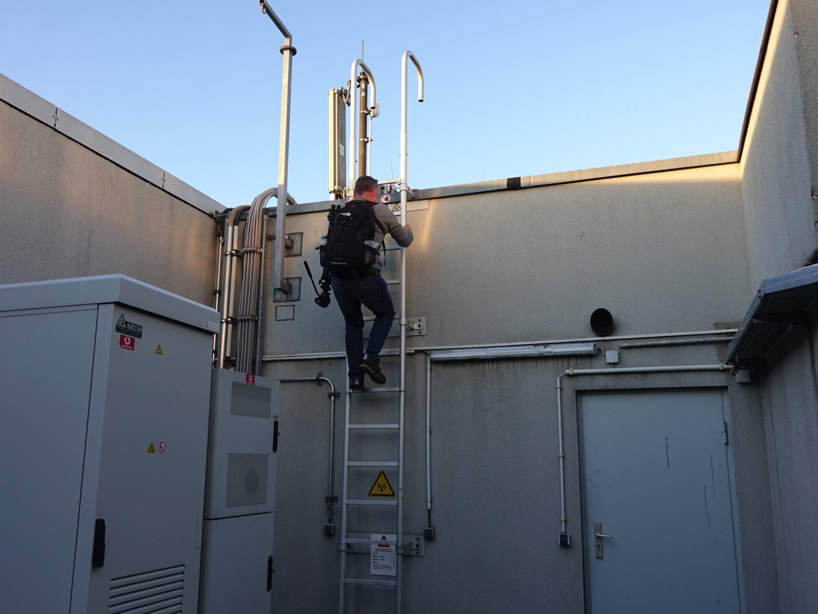 Mann klettert Leiter hinauf.