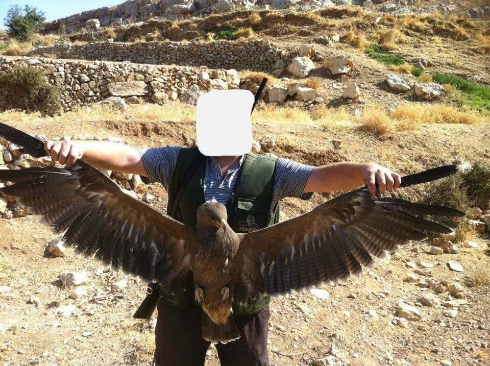 Ein Vogelwilderer präsentiert stolz einen geschossenen Schreiadler