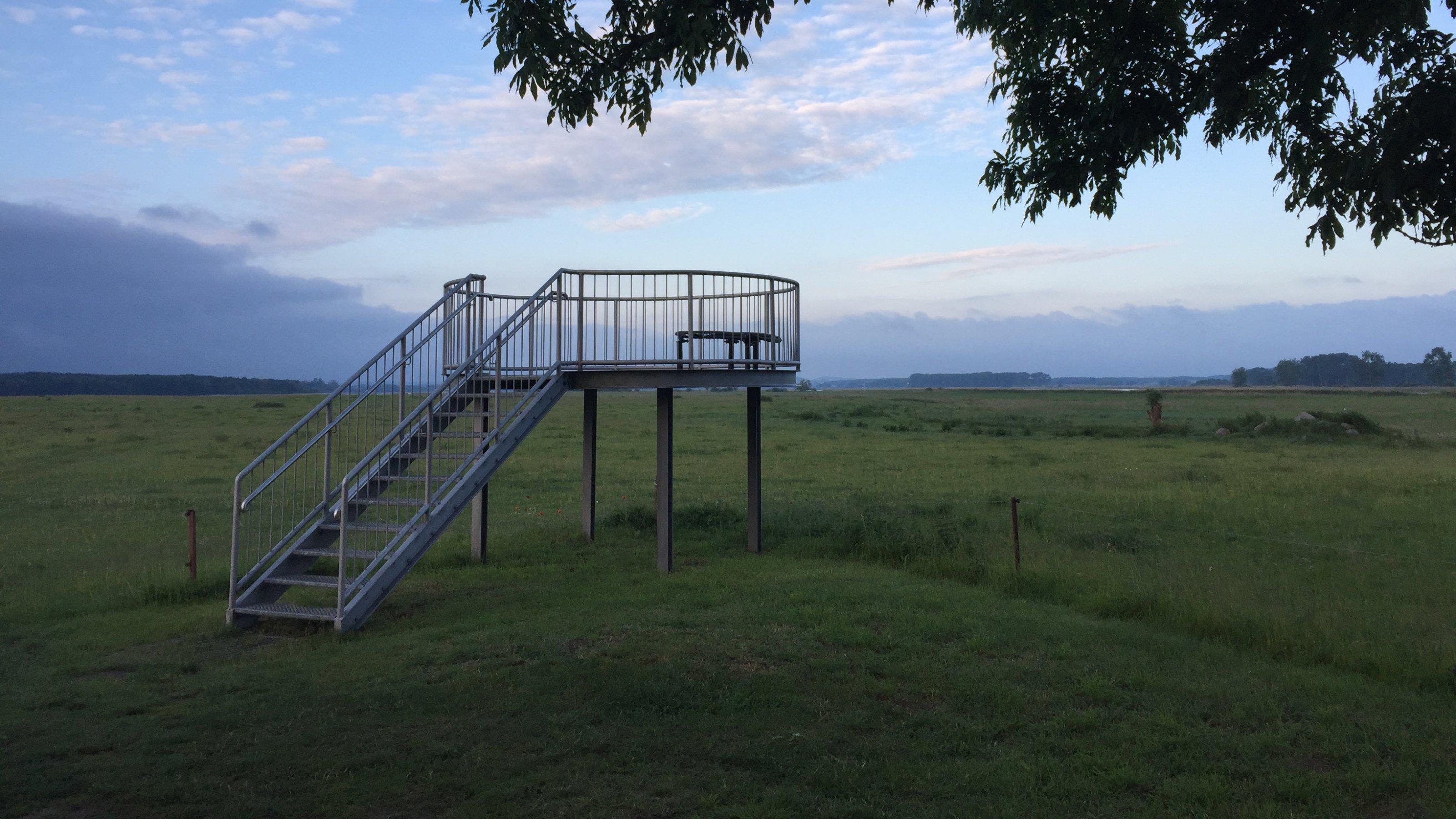 Eine kleine Aussichtsplattform steht an einem großen freien Feld.