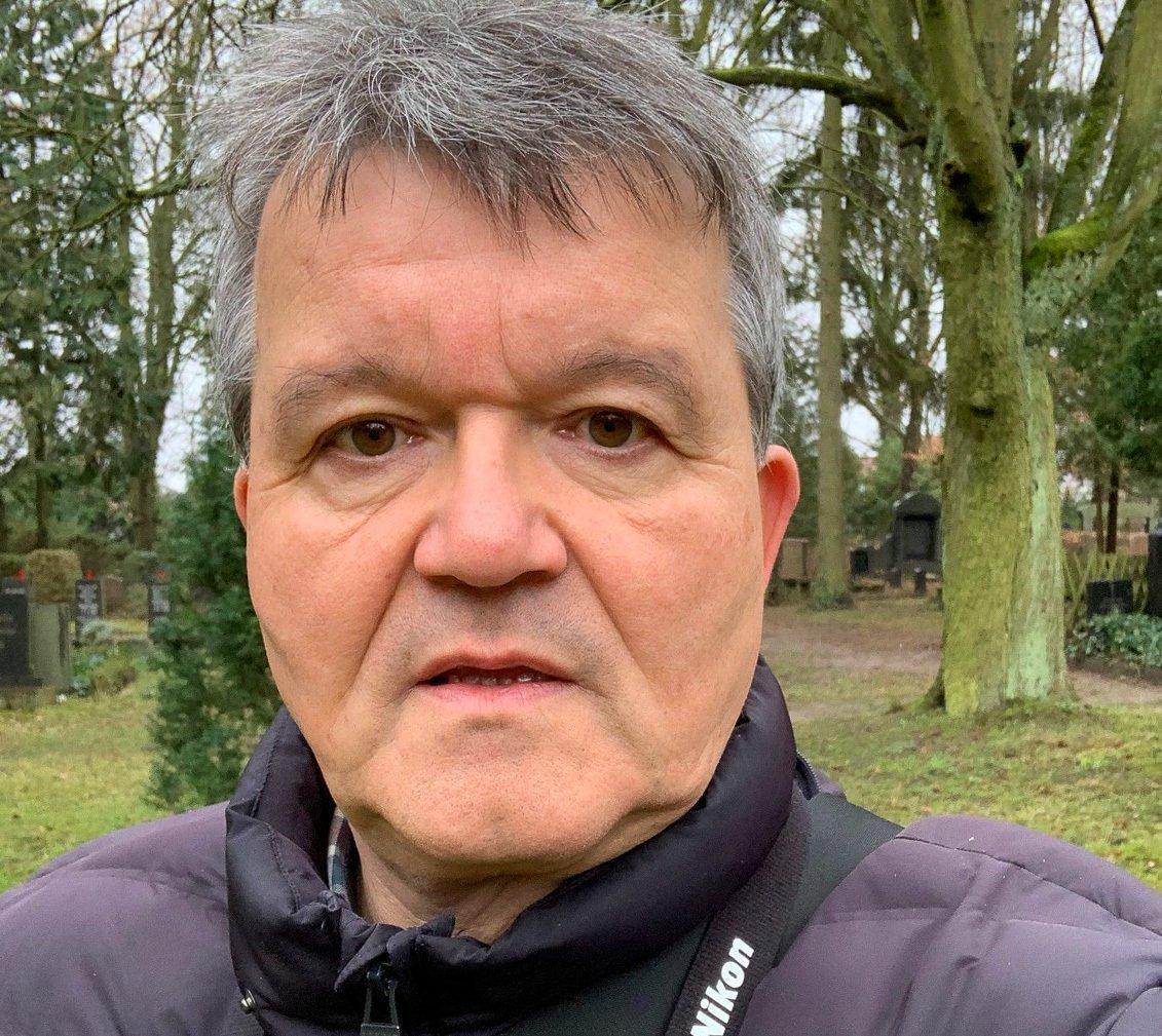 Portrait eines grauhaarigen Mannes. Im Hintergrund winterlich kahle Bäume in einem Park.